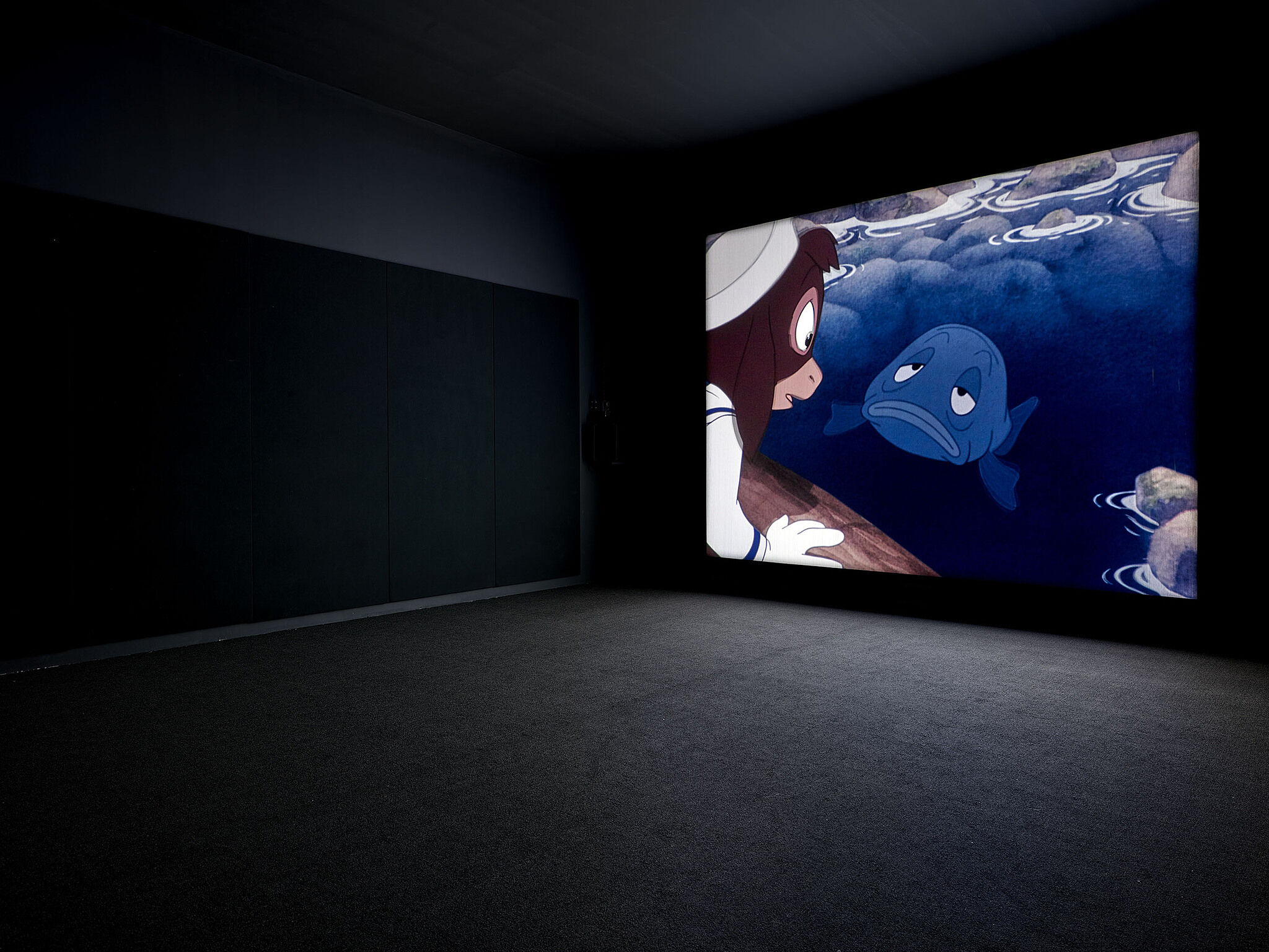 A video screen shows a fish and animals on the wall of a gallery.