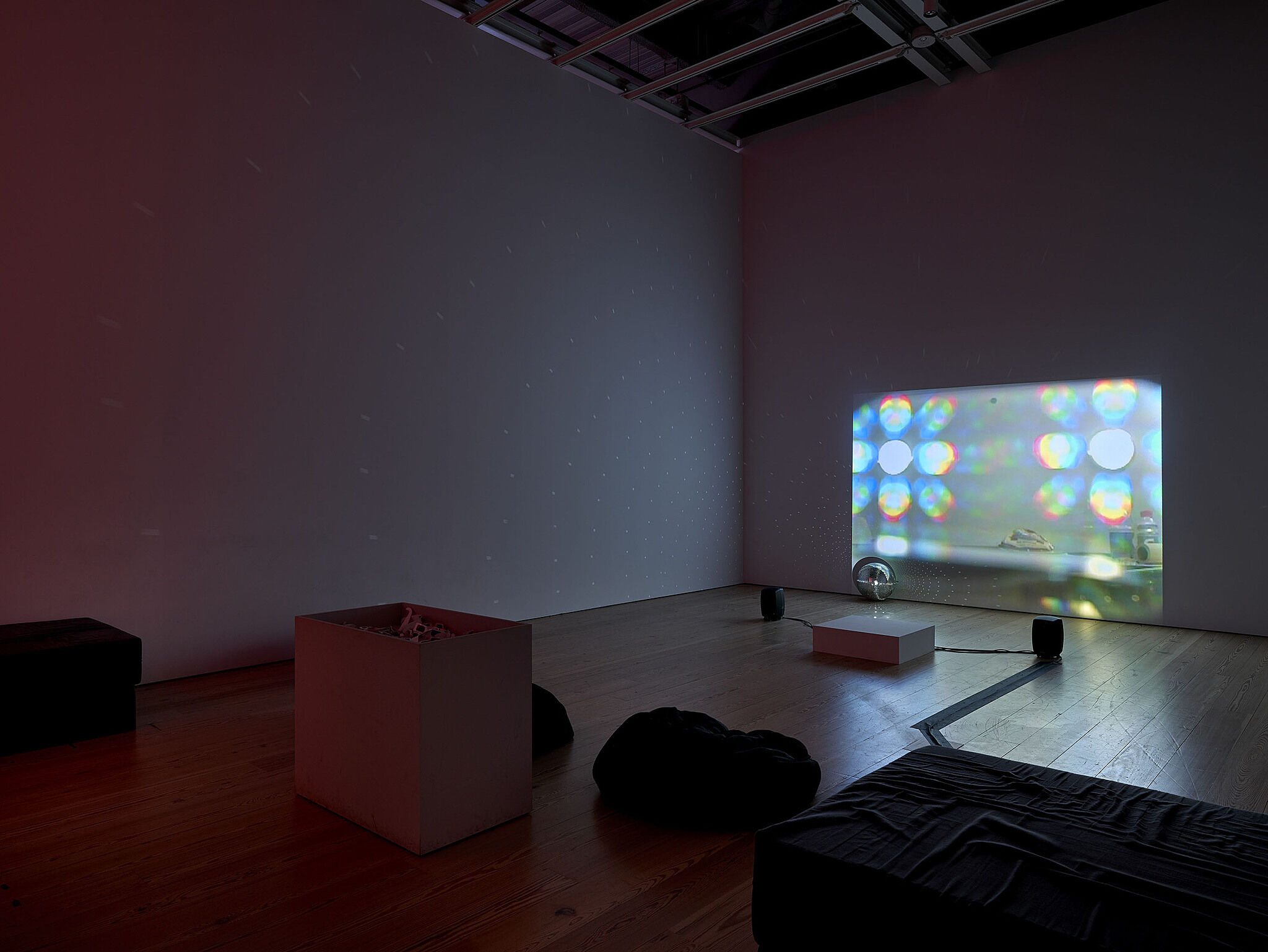 A video installation with a screen showing bright shapes of light.