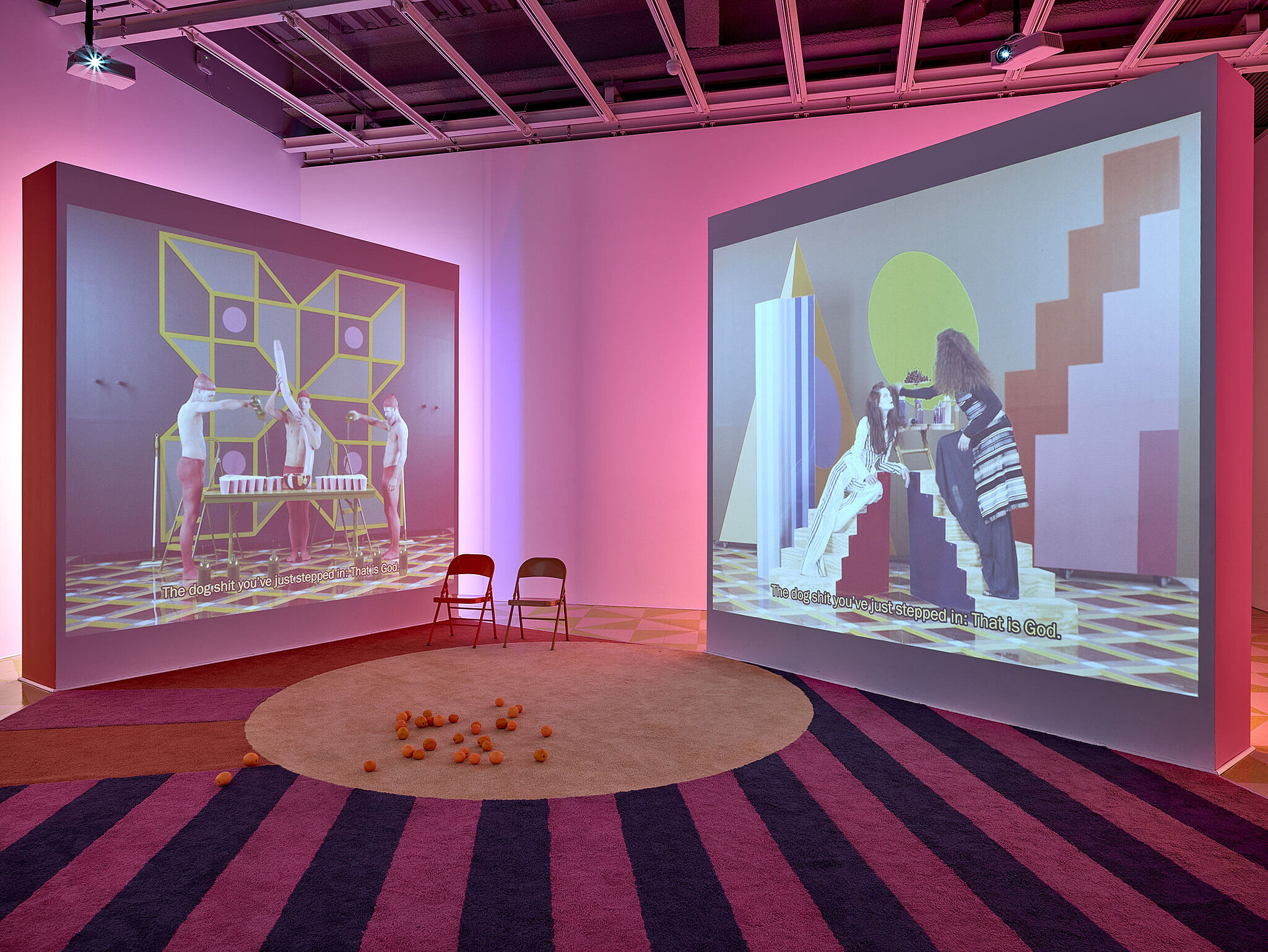 Two screens showing videos with two chairs in a gallery with pink lighting.