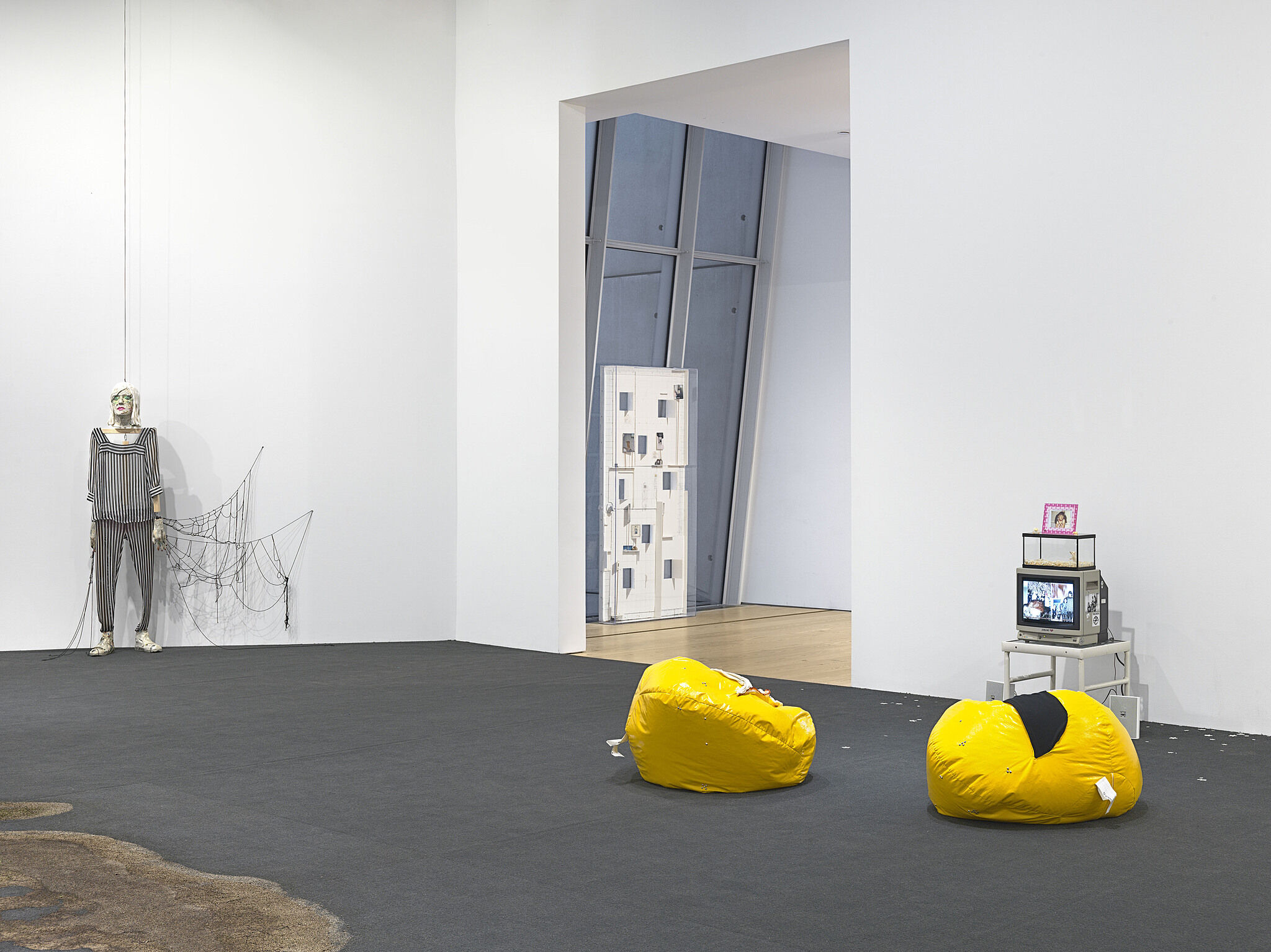 Yellow beanbag chairs sit on the ground with installation surrounding it.