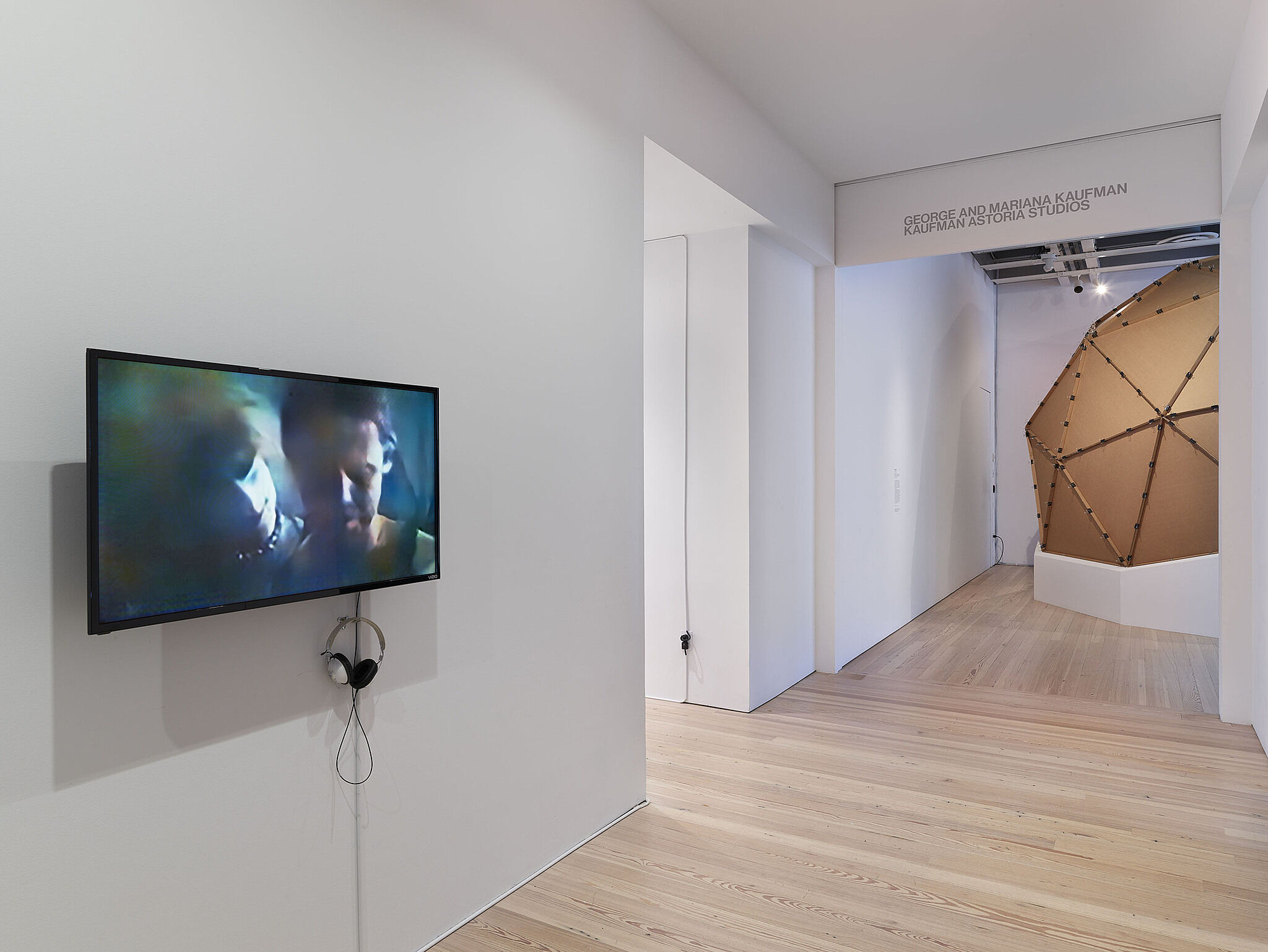 A video installation with a flat screen television showing two faces.