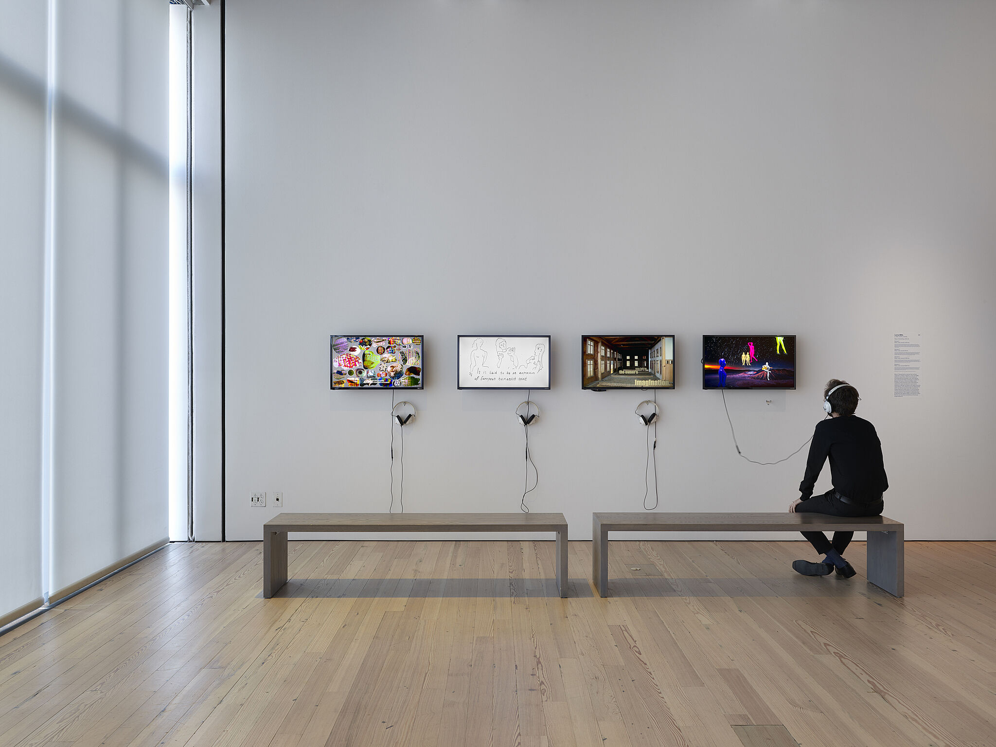 A man sits on a bench in front of four video screens on a gallery wall.