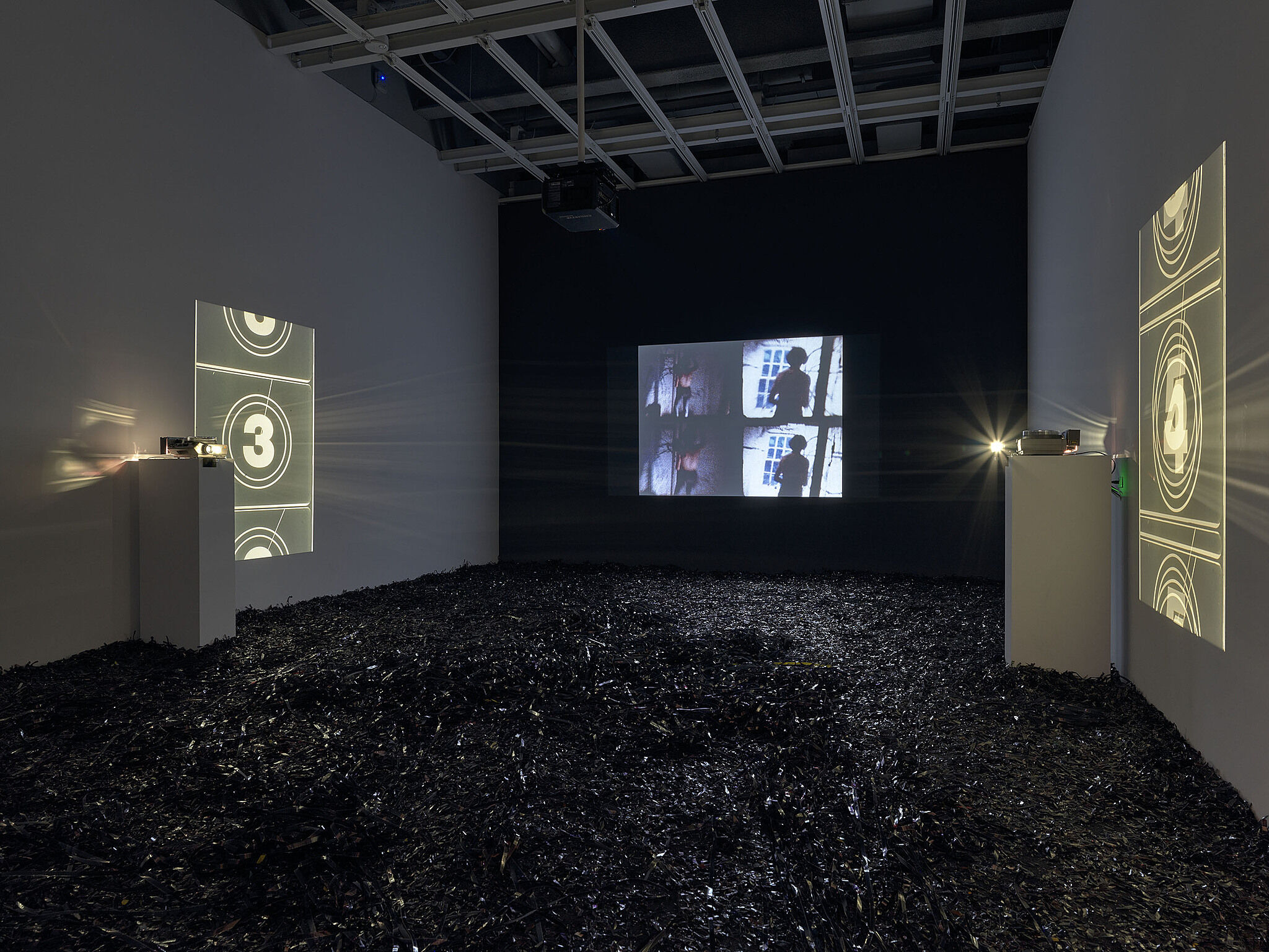 An installation view with three projection screens and black material on the floor.