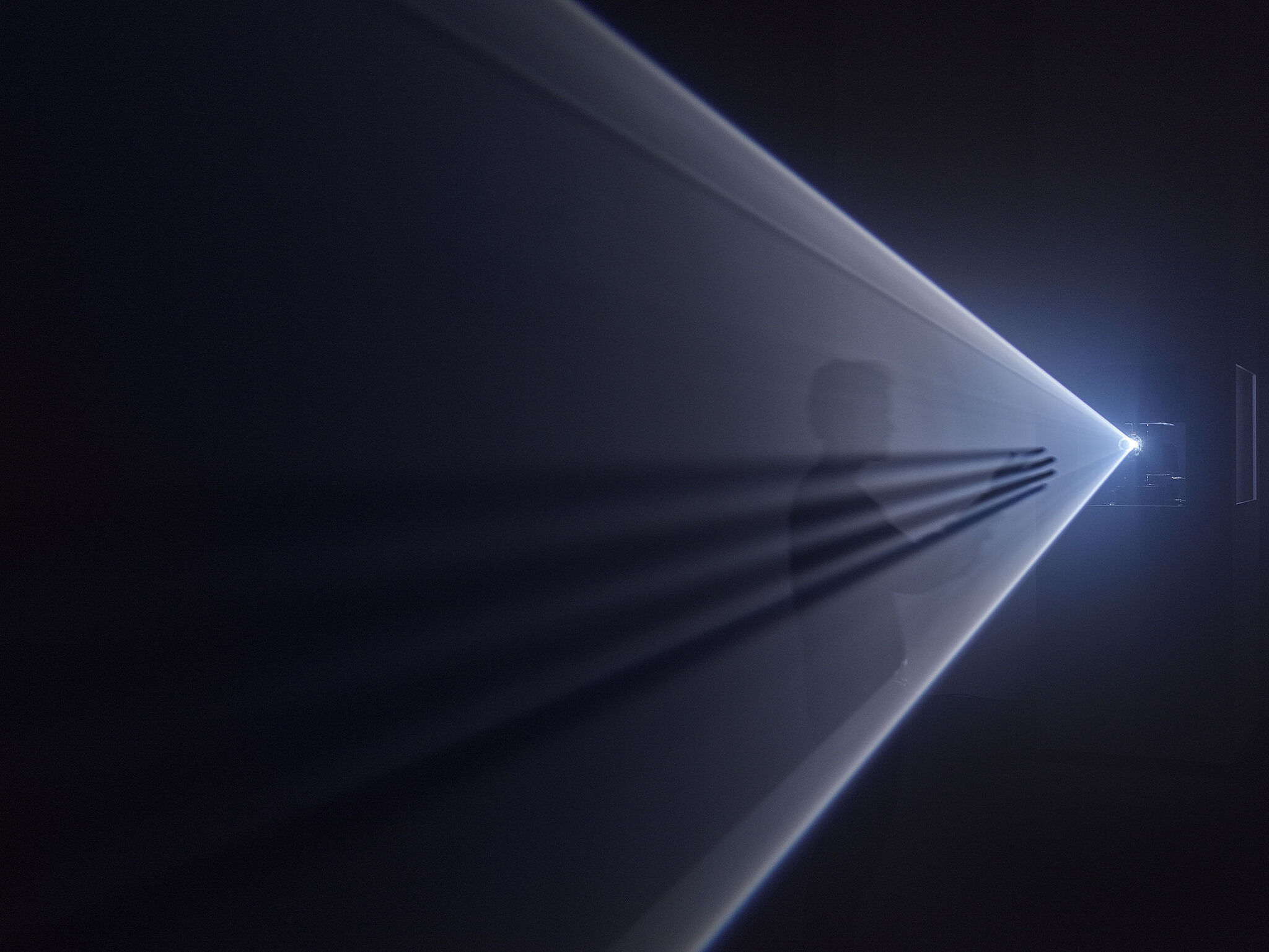 A person stands in the middle of a beam of light from a projector.