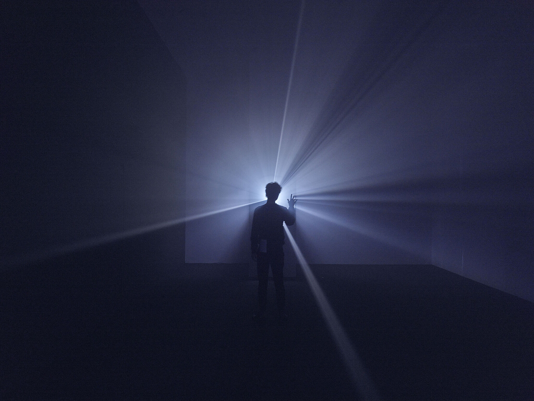 A man stands in front of a film projector diffusing a beam of light.