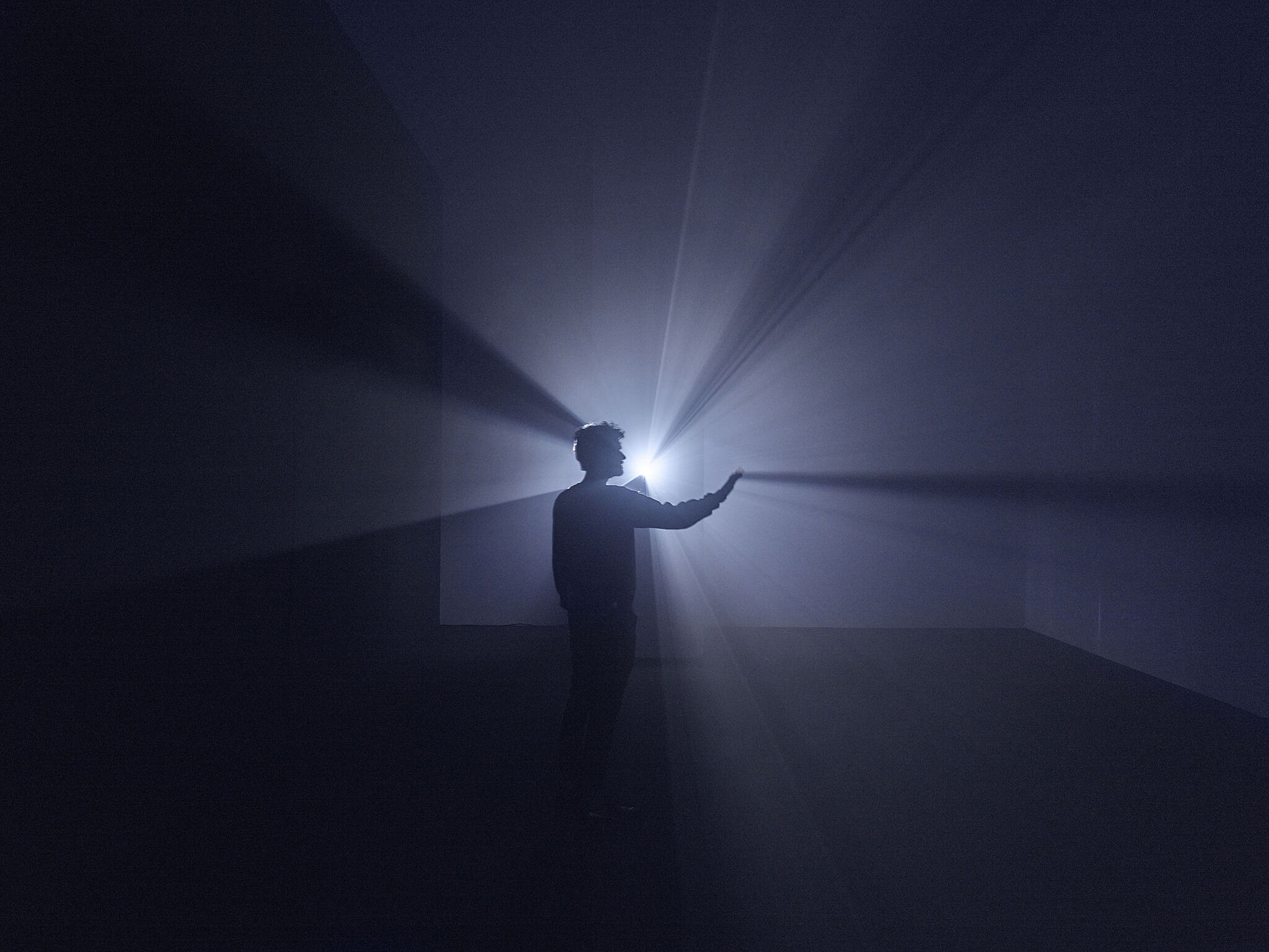 A man stands in front of a projector blocking a beam of light.