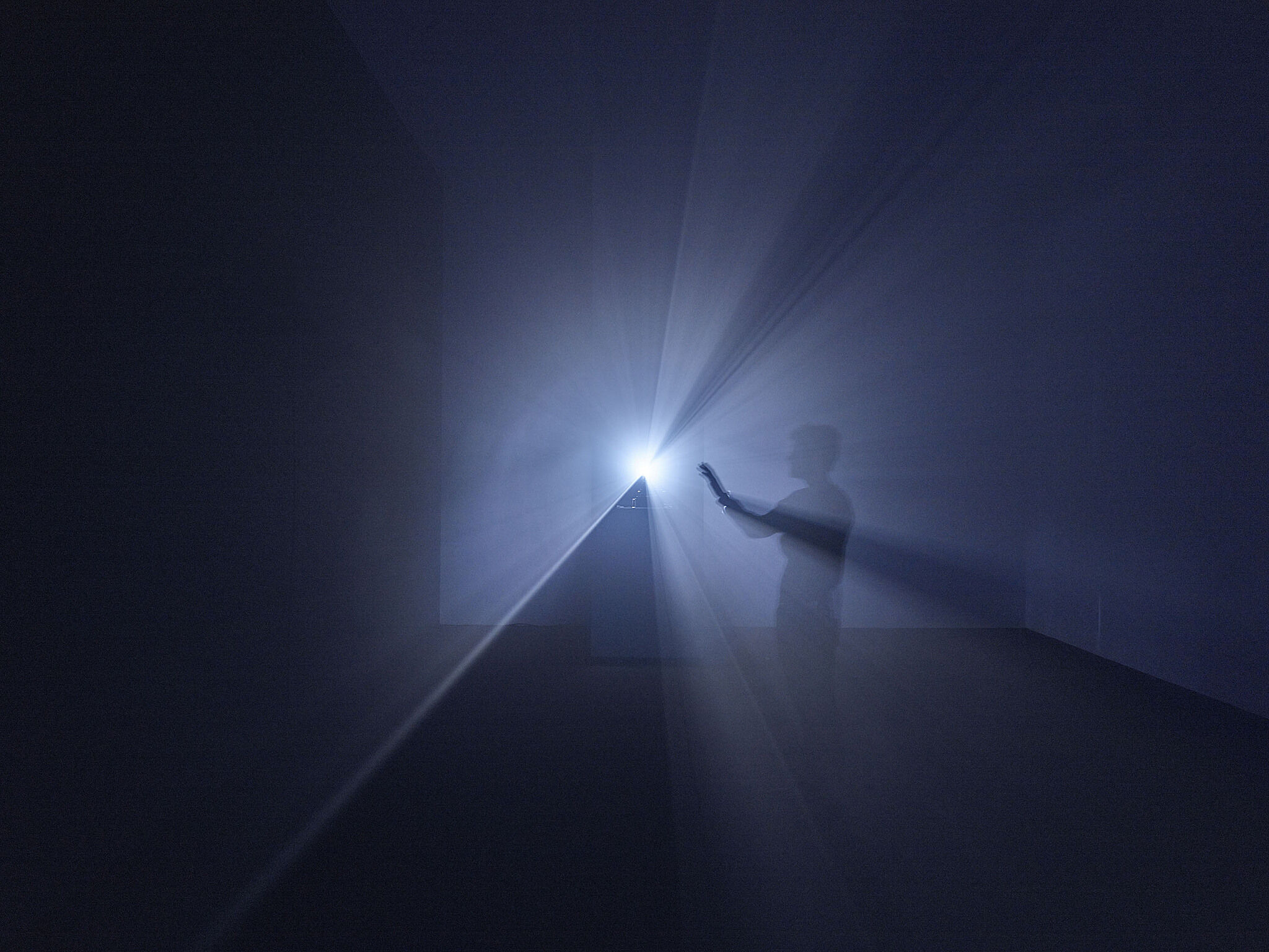 A man holds his hand out towards a beam of light from a film projector.