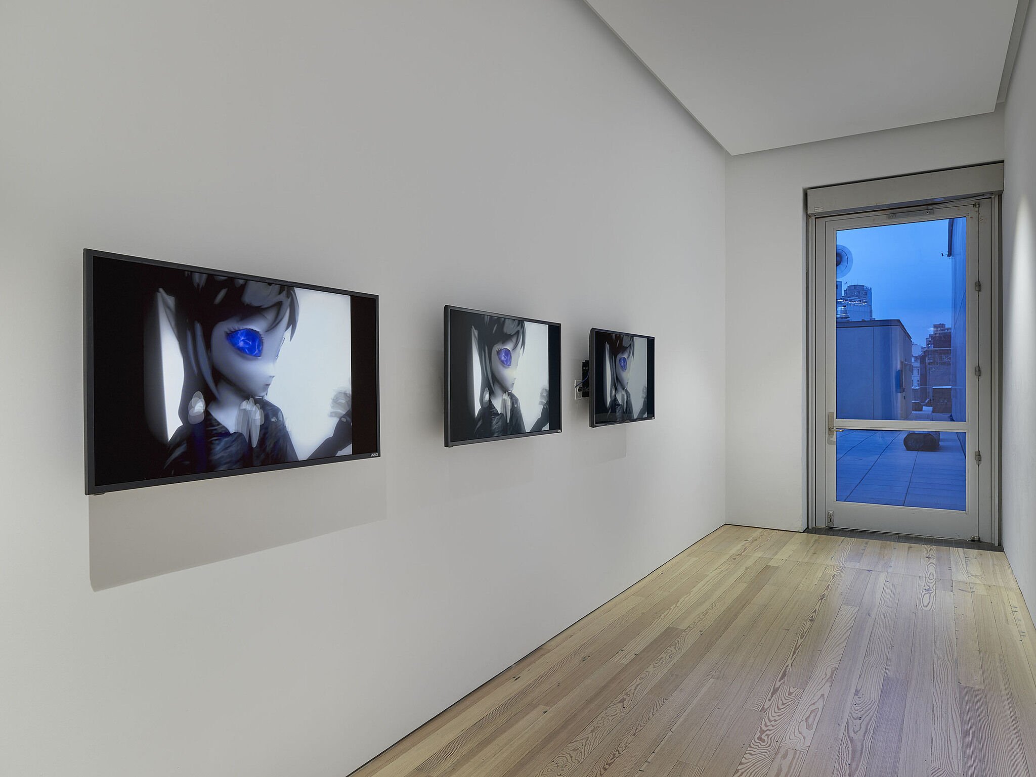 Three screens showing an alien figure on the wall of a gallery with a window.