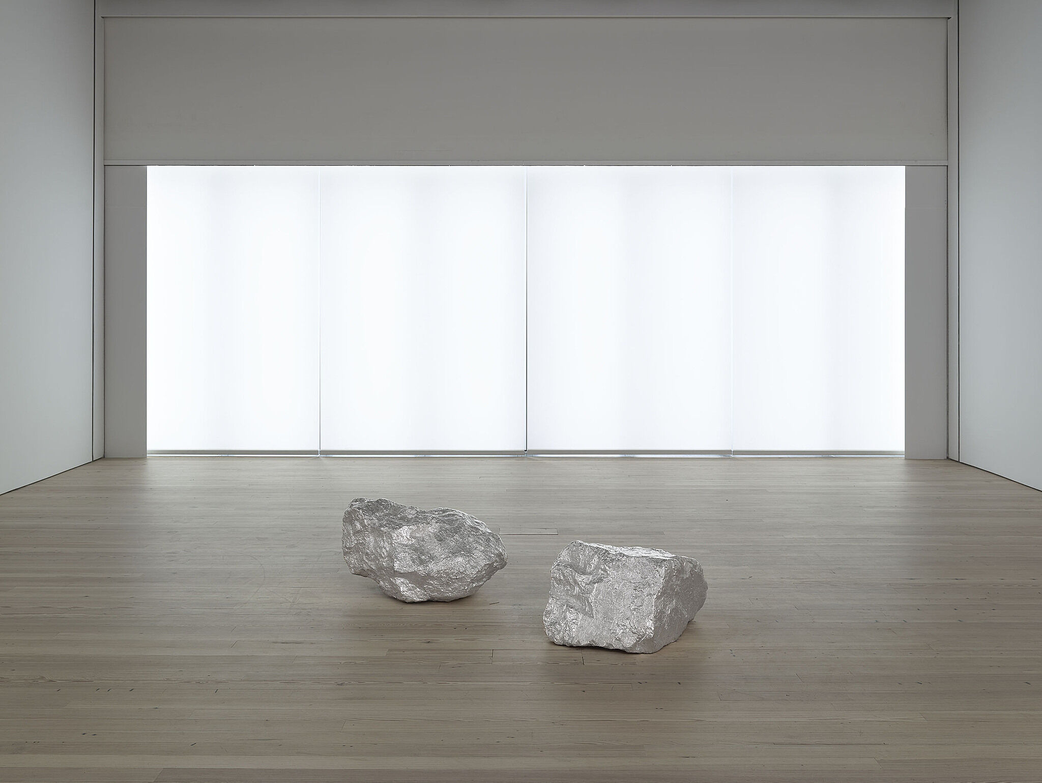 Two rocks  in the middle of a room with a bright light behind.