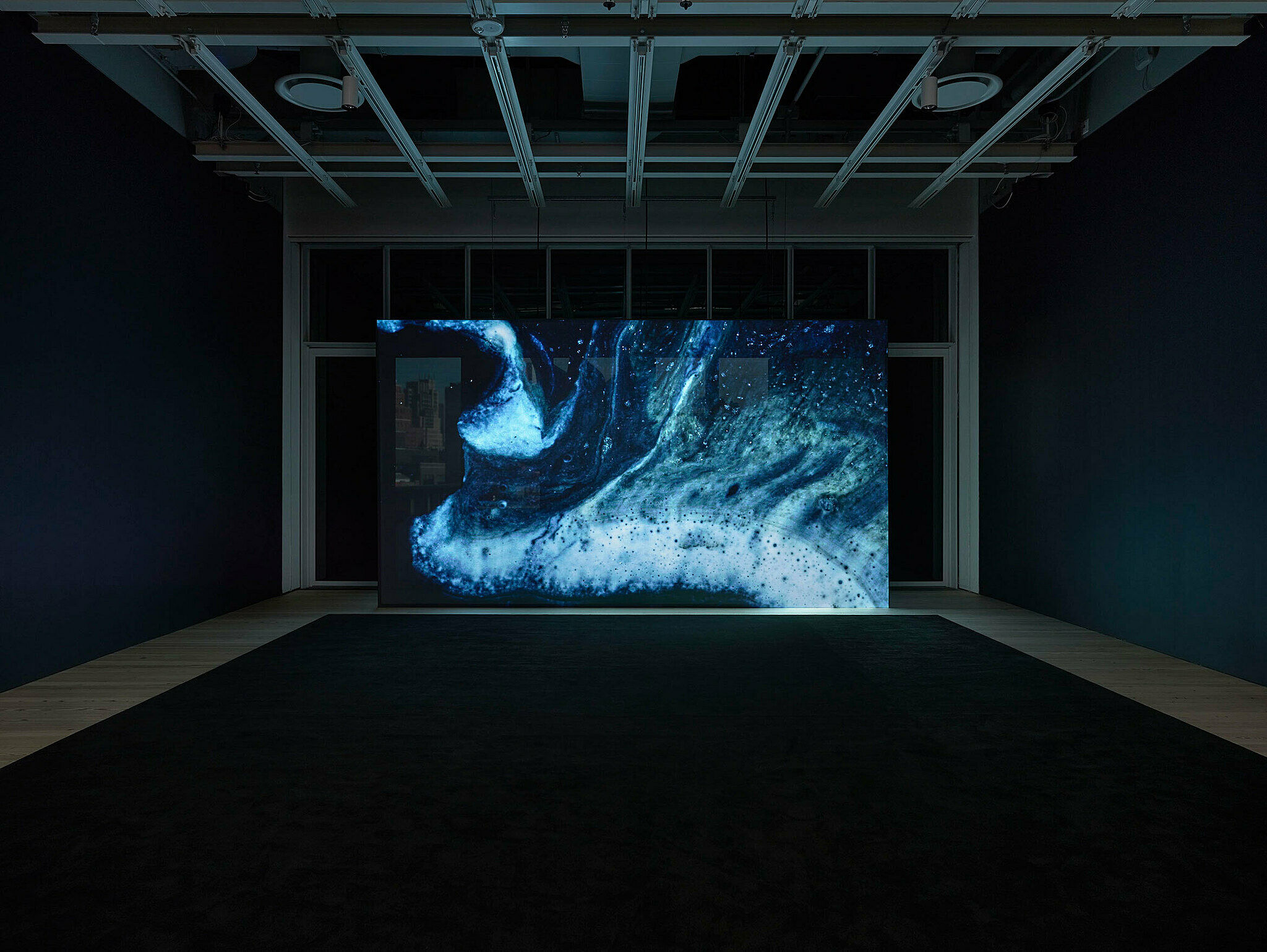 A darkened gallery with a large abstract artwork on the wall.