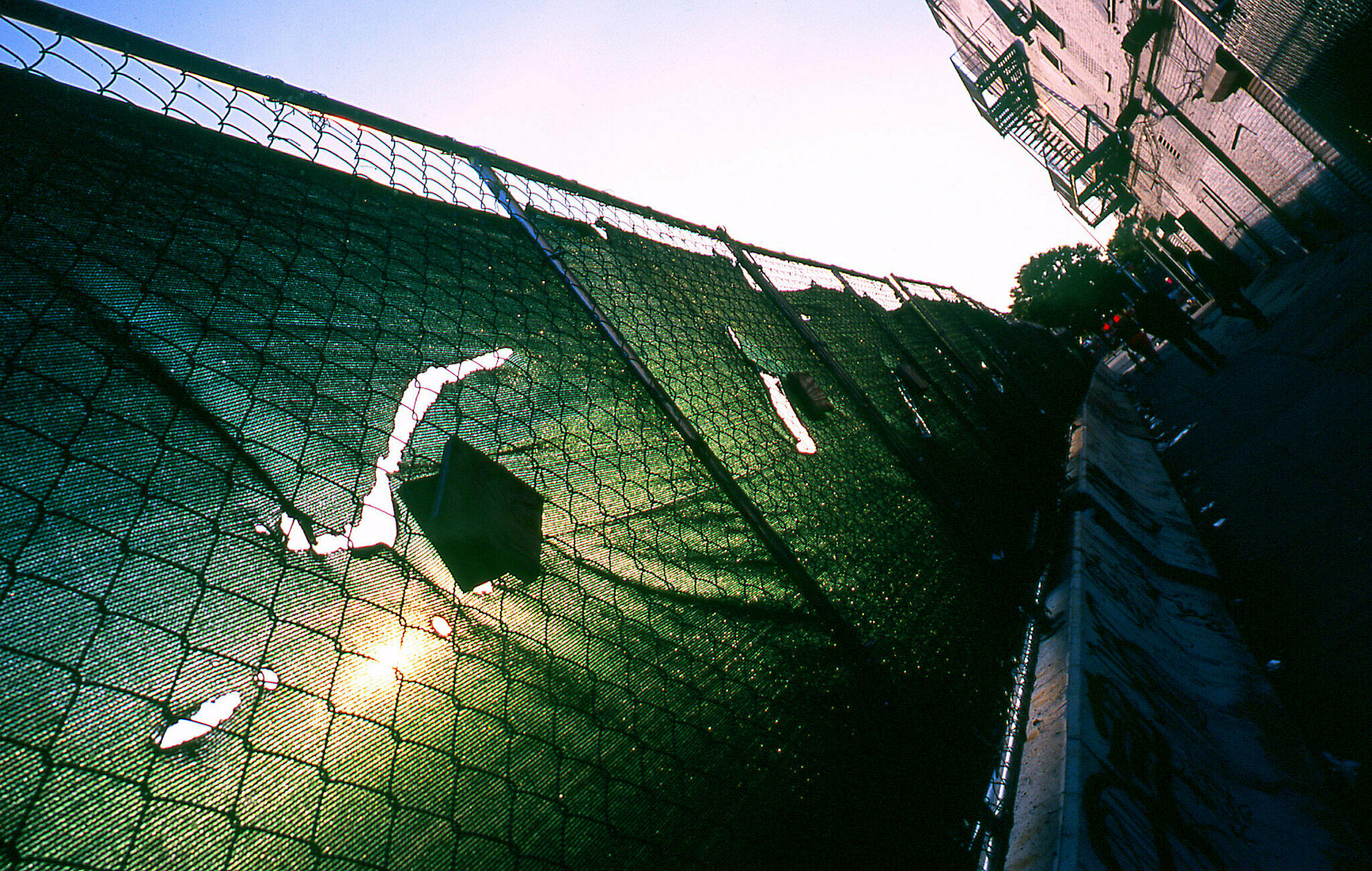 A green fabric covers an outdoor fence with the sun shining through.