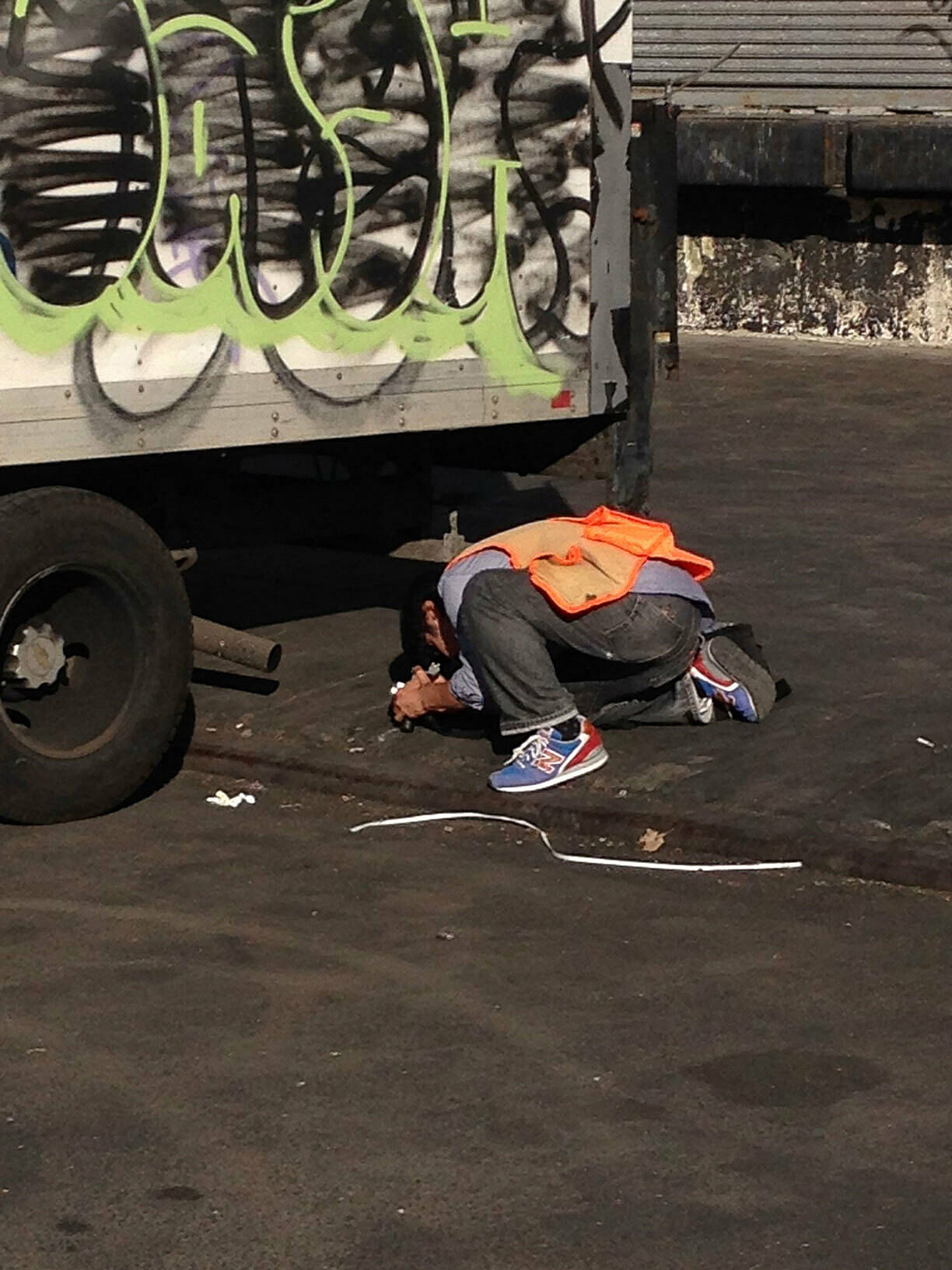 A man in an orange vest bends down below a truck.