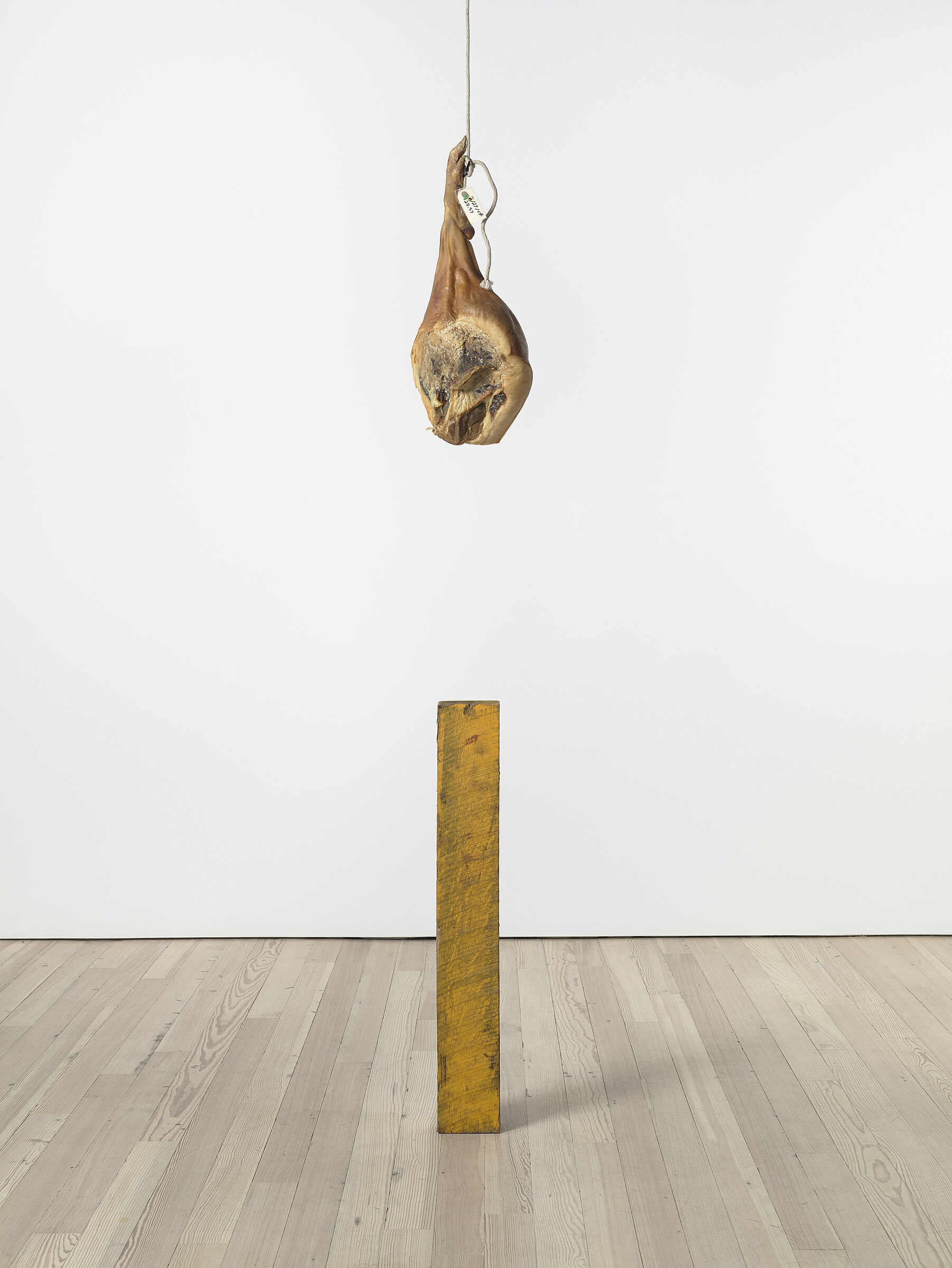 An art installation of a leg of ham hanging over a yellow pole.