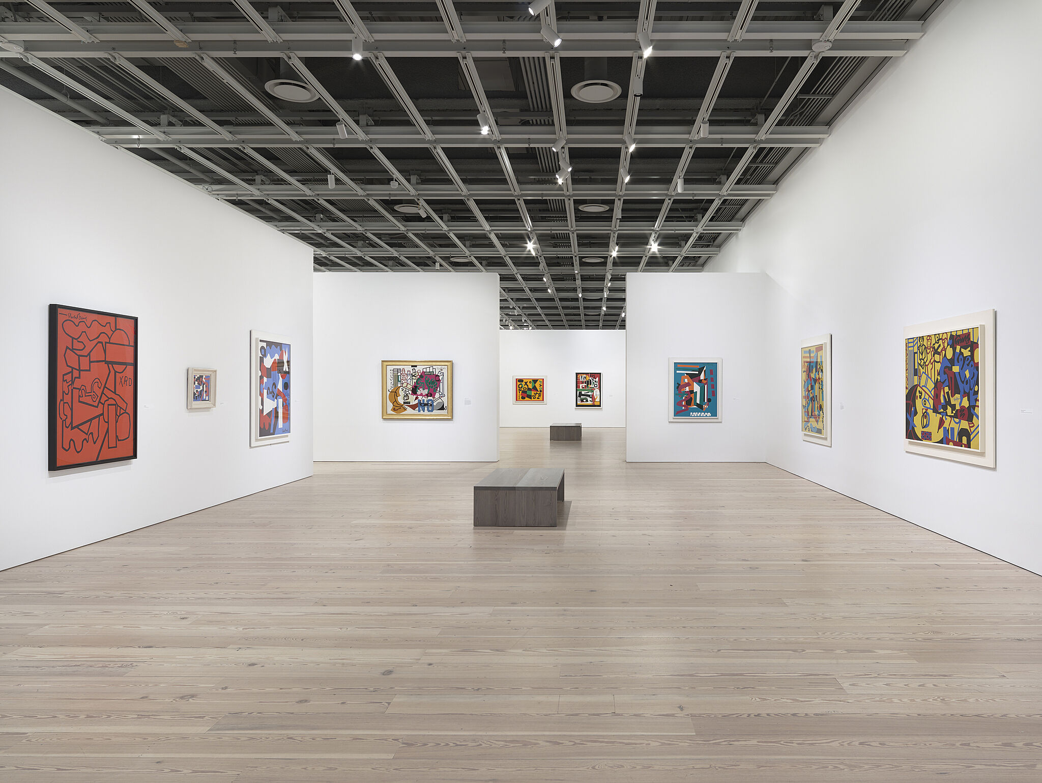Large gallery space with paintings hanging on walls.