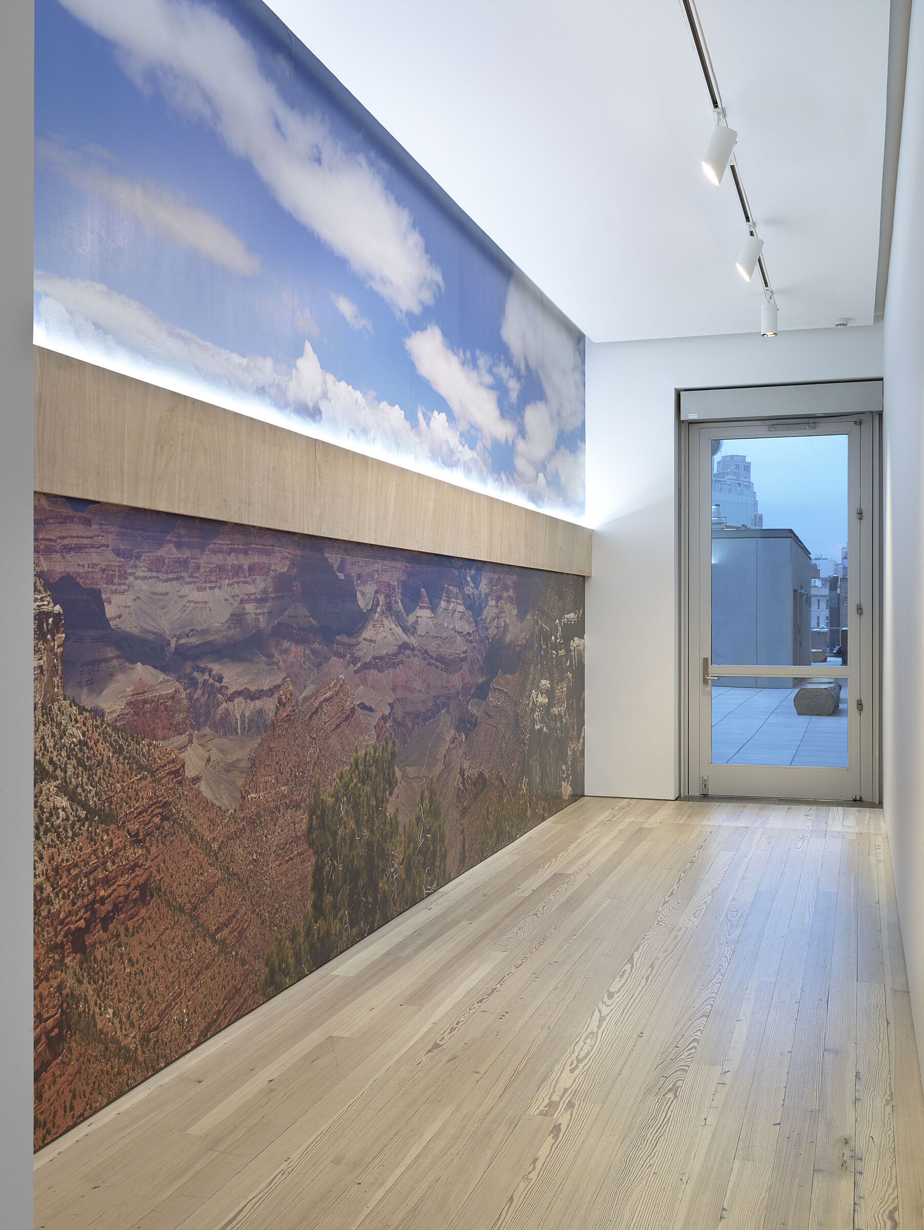 An art installation on a wall with clouds on top and an image of the Grand Canyon below.