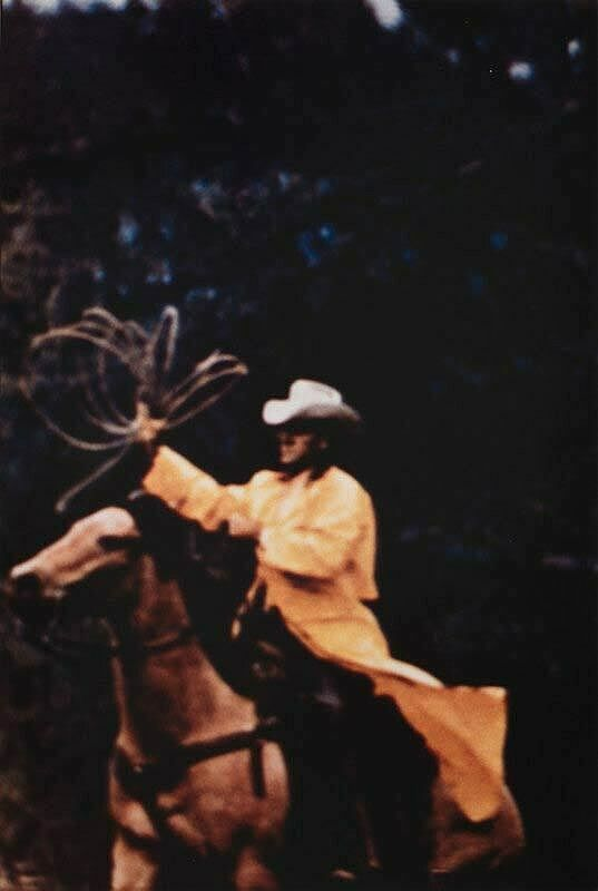 A cowboy in a raincoat sitting on a horse with a rope in his hand.