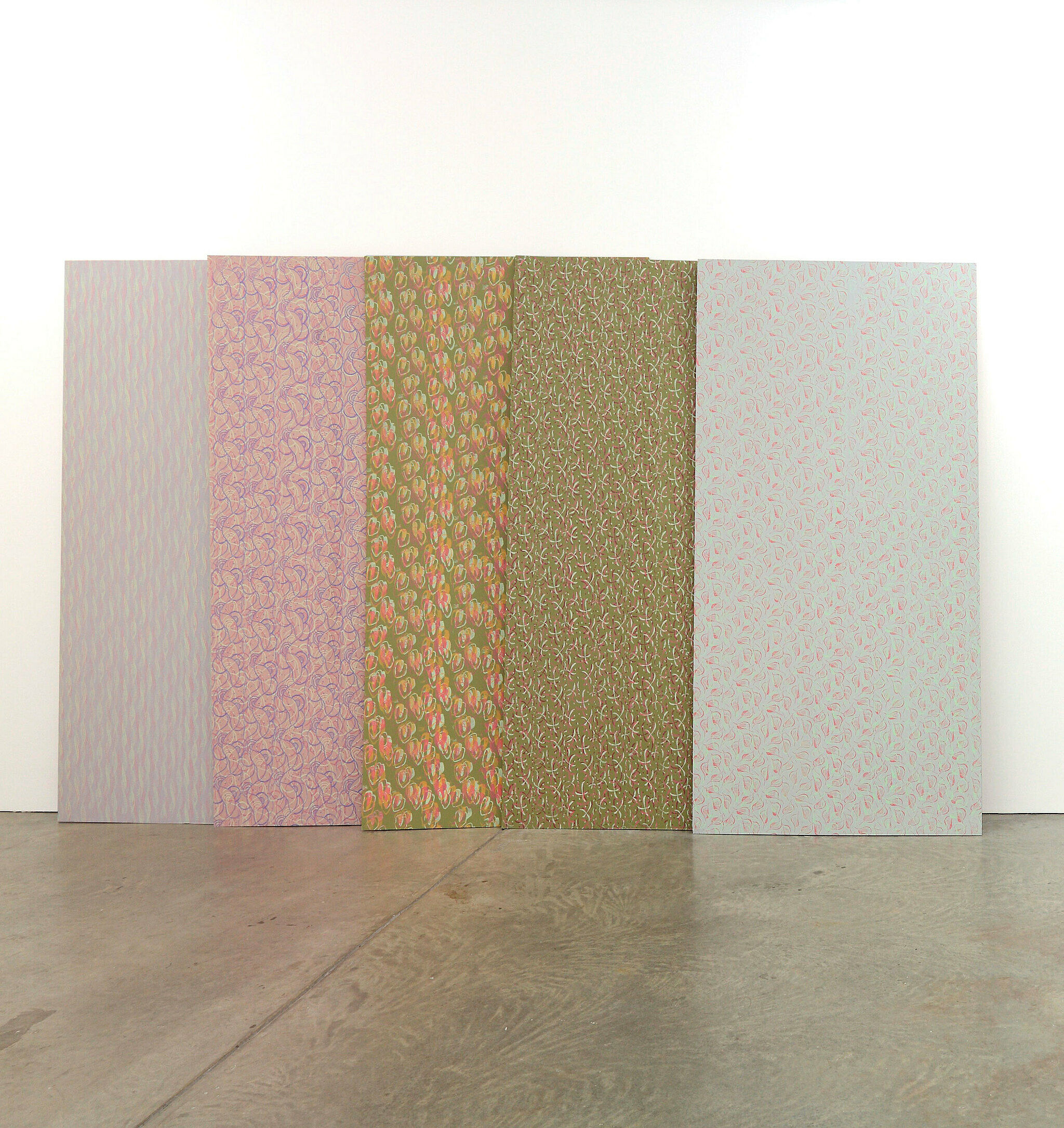 An artwork by Marc-Camille Chaimowicz standing on a gallery floor with five panels of plywood with fabric on it.