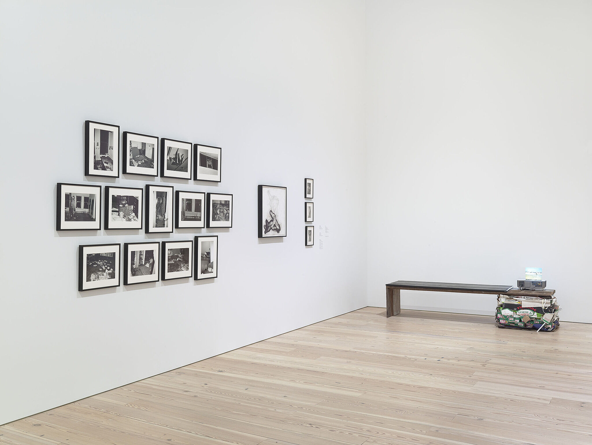 A series of photos on the wall and a sculpture on the floor.