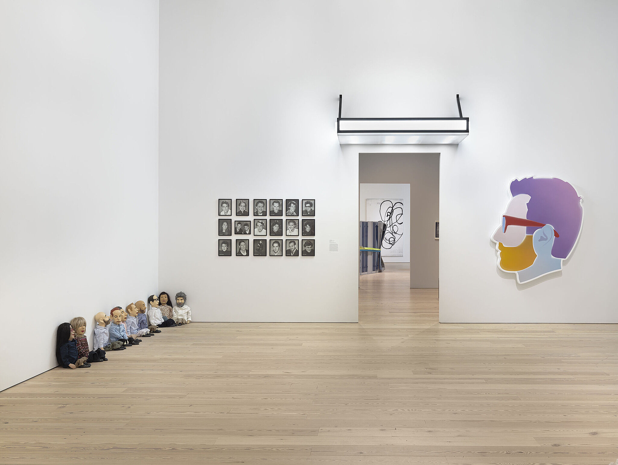A series of dolls on the left side of the gallery and other artwork on the wall.