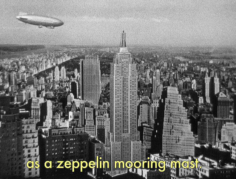 Black and white still of a Zeppelin flying over Manhattan.