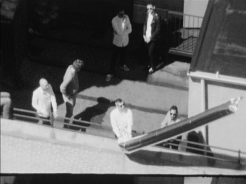 Black and white still of the top of a building.