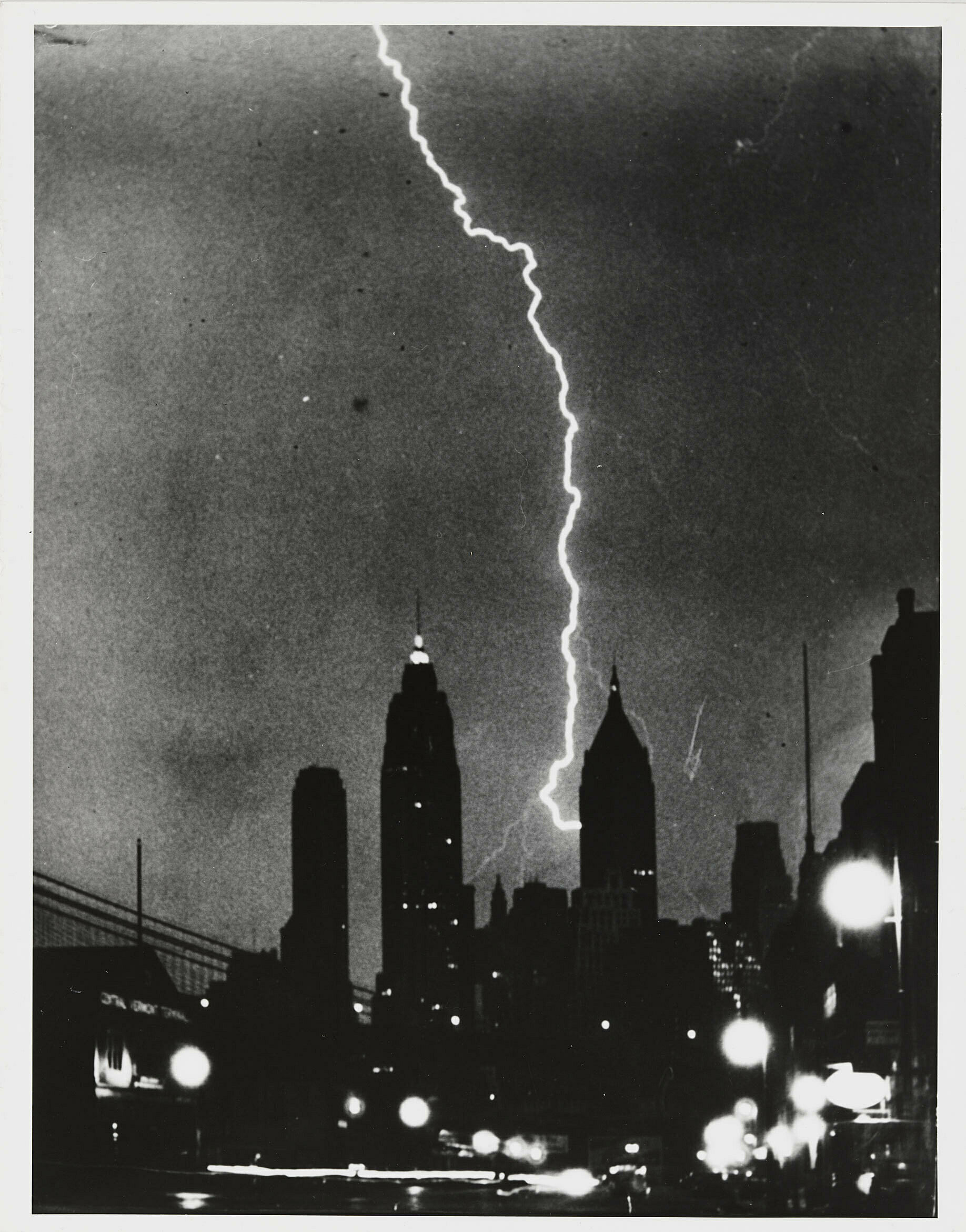 Black and white photo of lightning striking a building in the city.