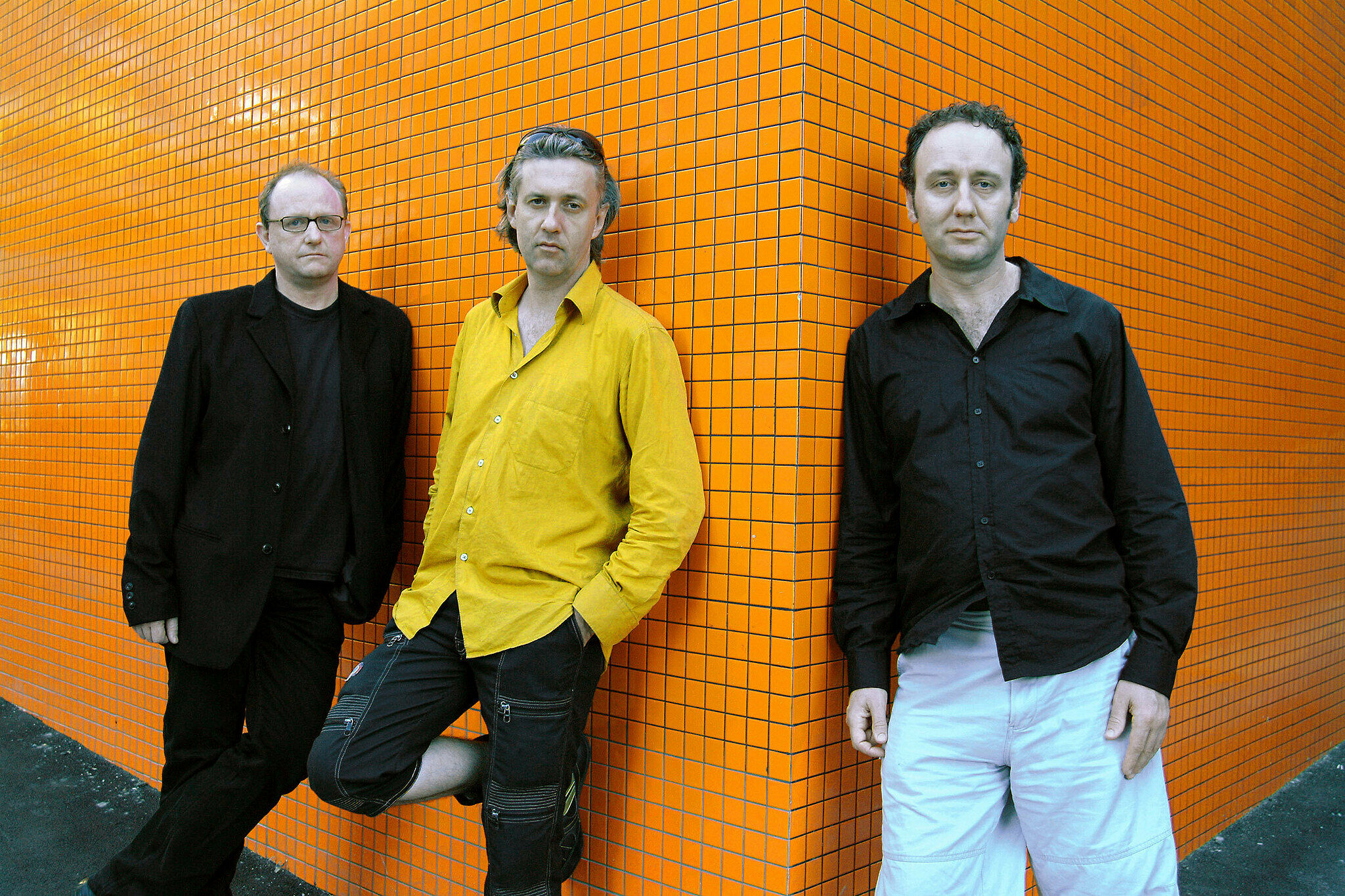 The Necks band leaning against an orange wall.