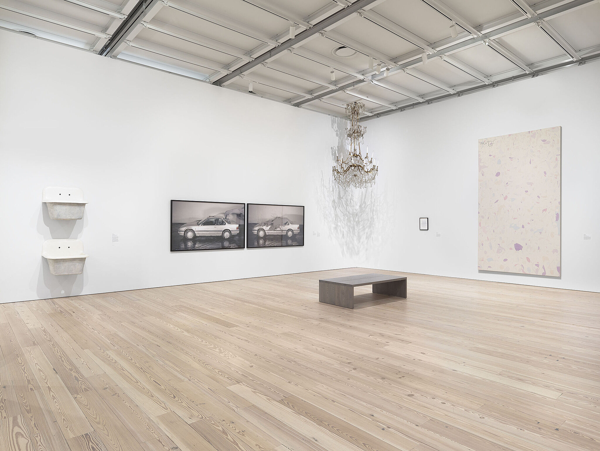 A wide view of a gallery with two sinks, two photos of cars, a hanging sculpture and large-scale painting.