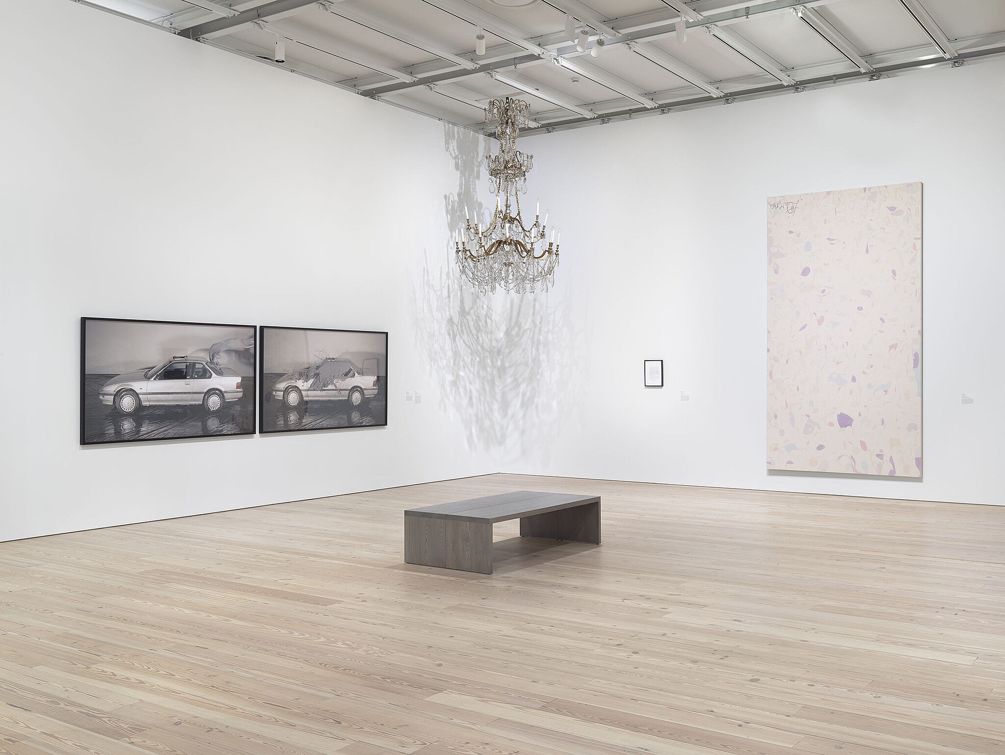 A bench sits in front of two photos of cars, a hanging sculpture and a large-scale painting on the wall.