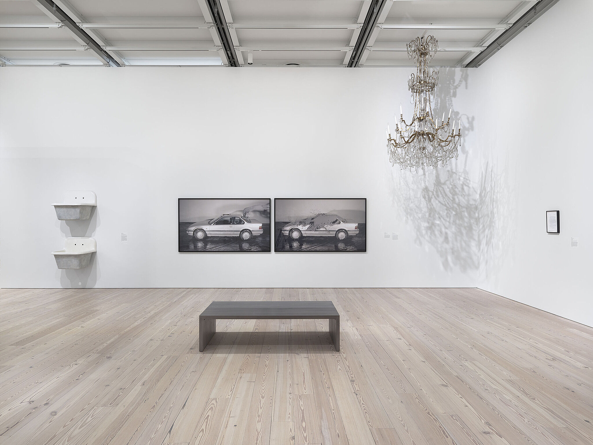 Art installation with a photos of cars, a sculpture in the right hand corner and two sinks on the wall.