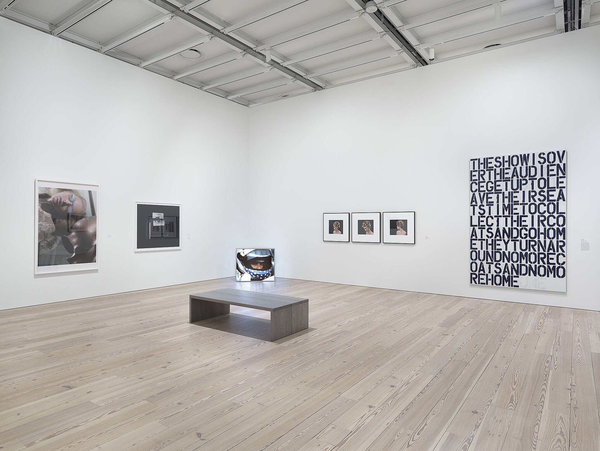 An installation view with a bend on the gallery floor and art on the walls.
