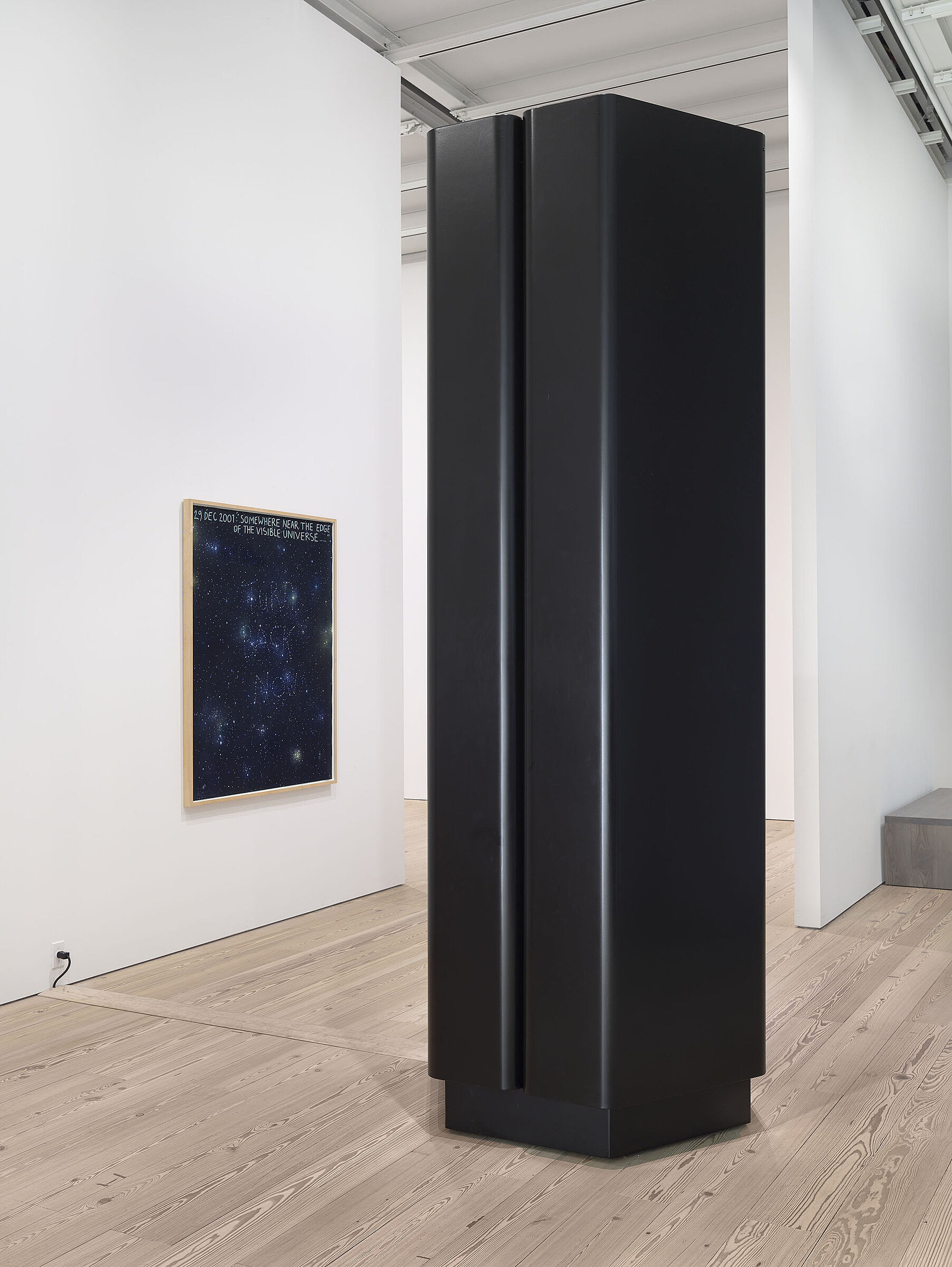 A black sculpture in the shape of a column on the gallery floor.
