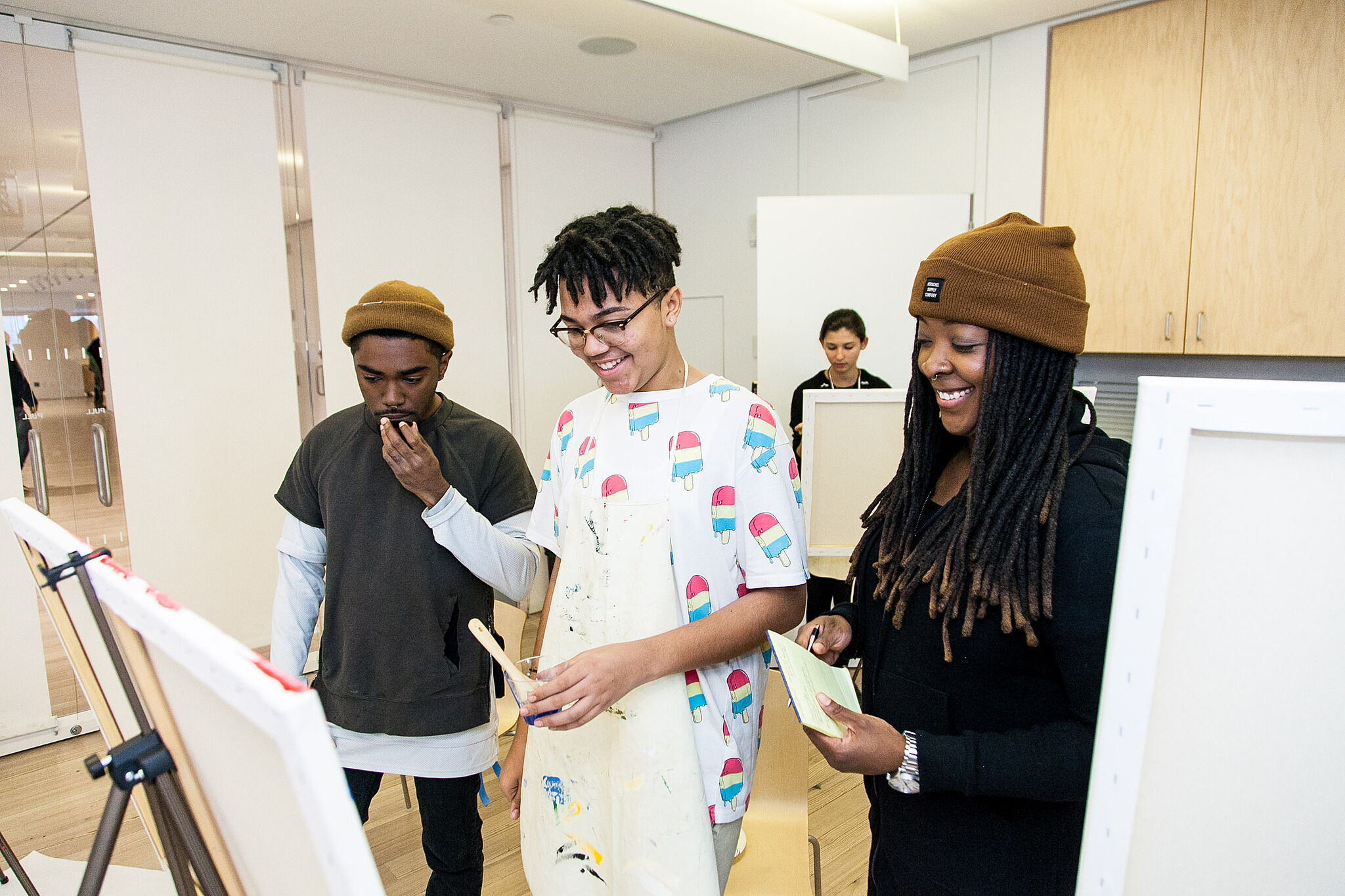 Artist and students stand in front of an easel.