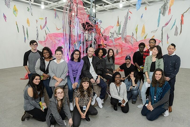 Exhibhition of students in front of art.