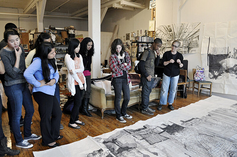 Students look at artwork on floor.