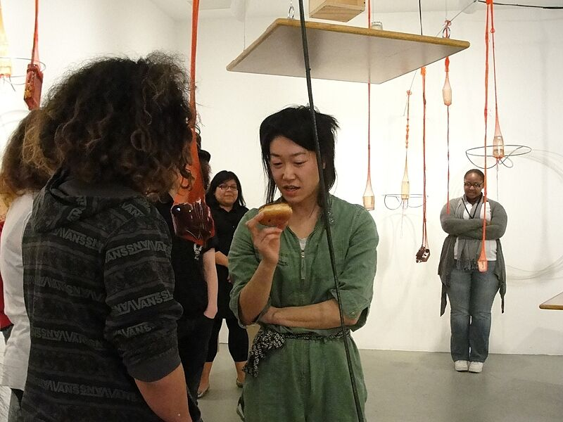Artist talking to students in a gallery.