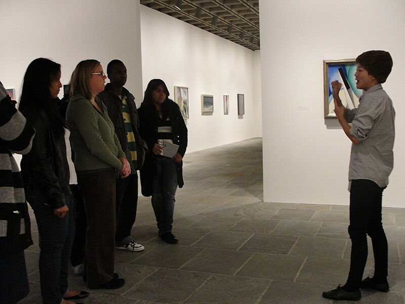 Artist talks to group of teens in gallery.
