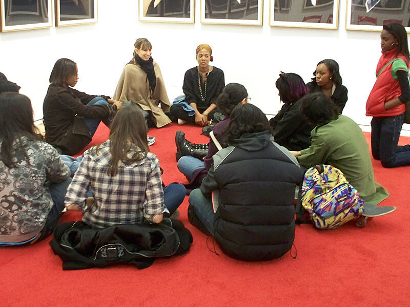 Students and teacher sit in a circle on the floor.