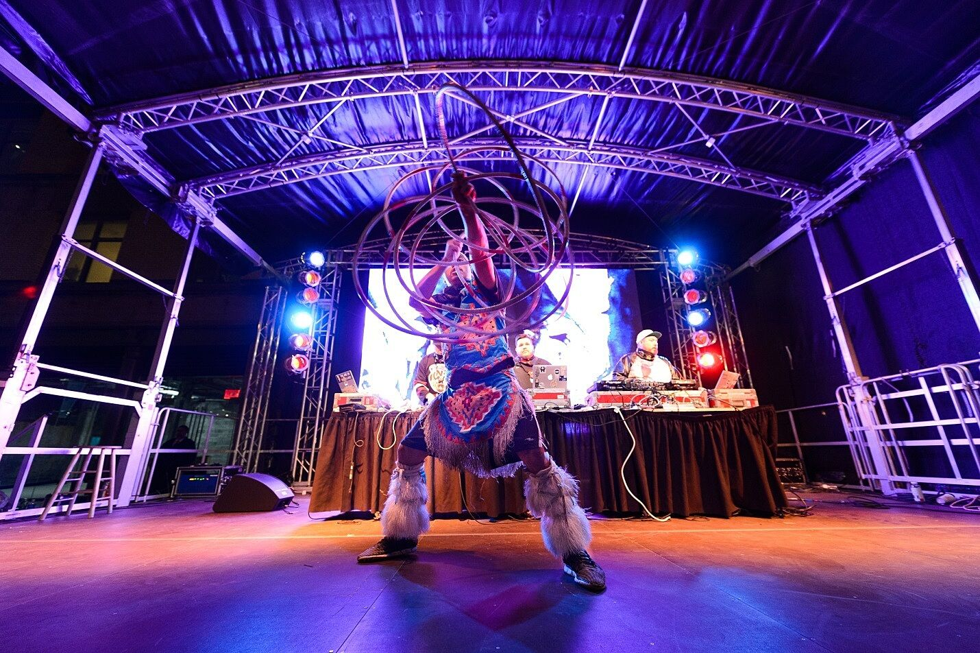 A Native American dancer performs in costume in front of a DJ booth.