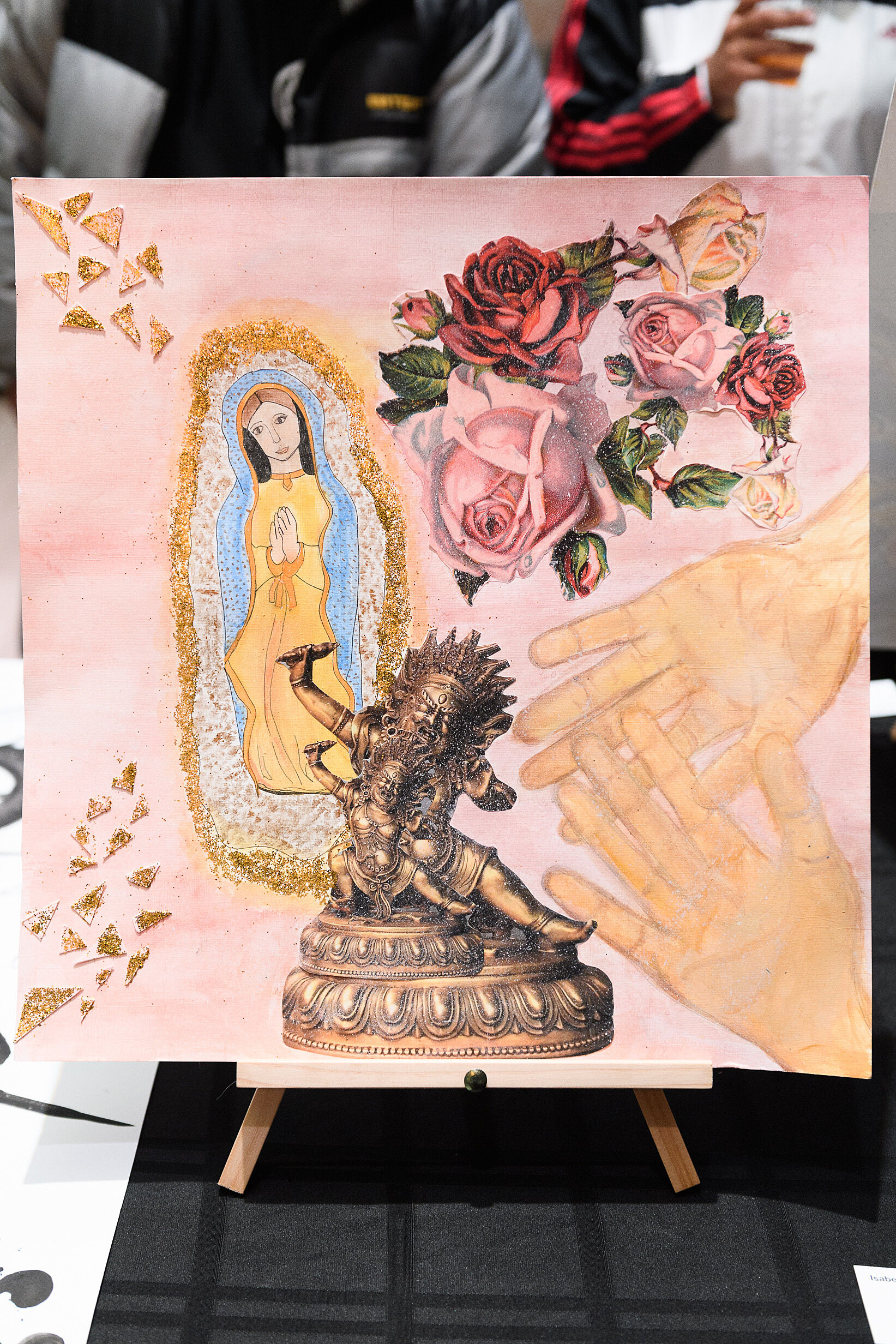 Hands, flowers, virgin mary and gold sparkles on a painting.