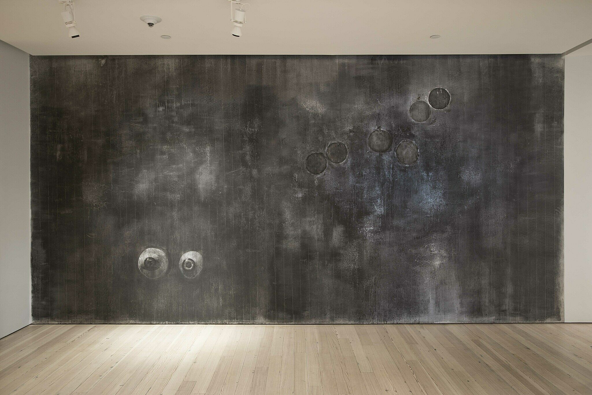 Gray textured wall with two eyes.