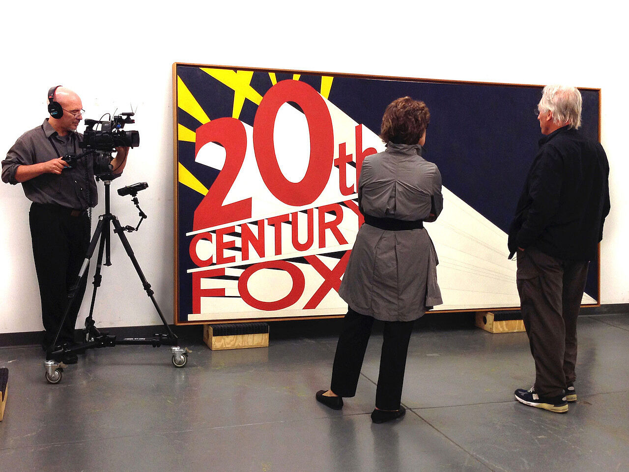 A photograph of people speaking in front of a camera and an artwork.