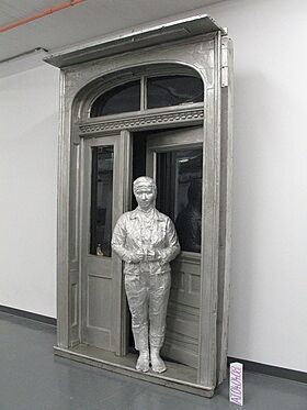A sculpture of a person standing in an open doorway.