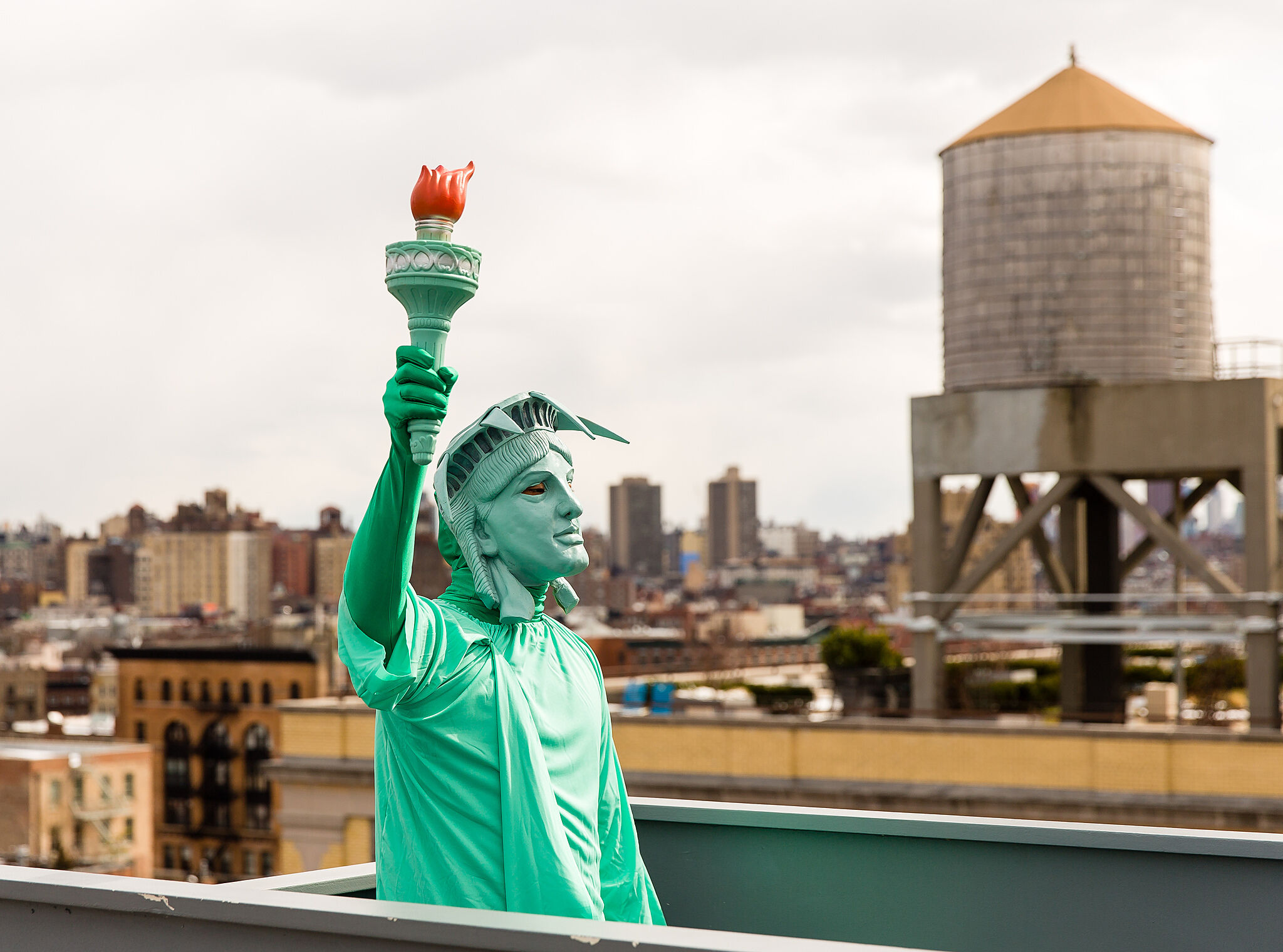 Person standing on balcony dressed as the Statue of Liberty