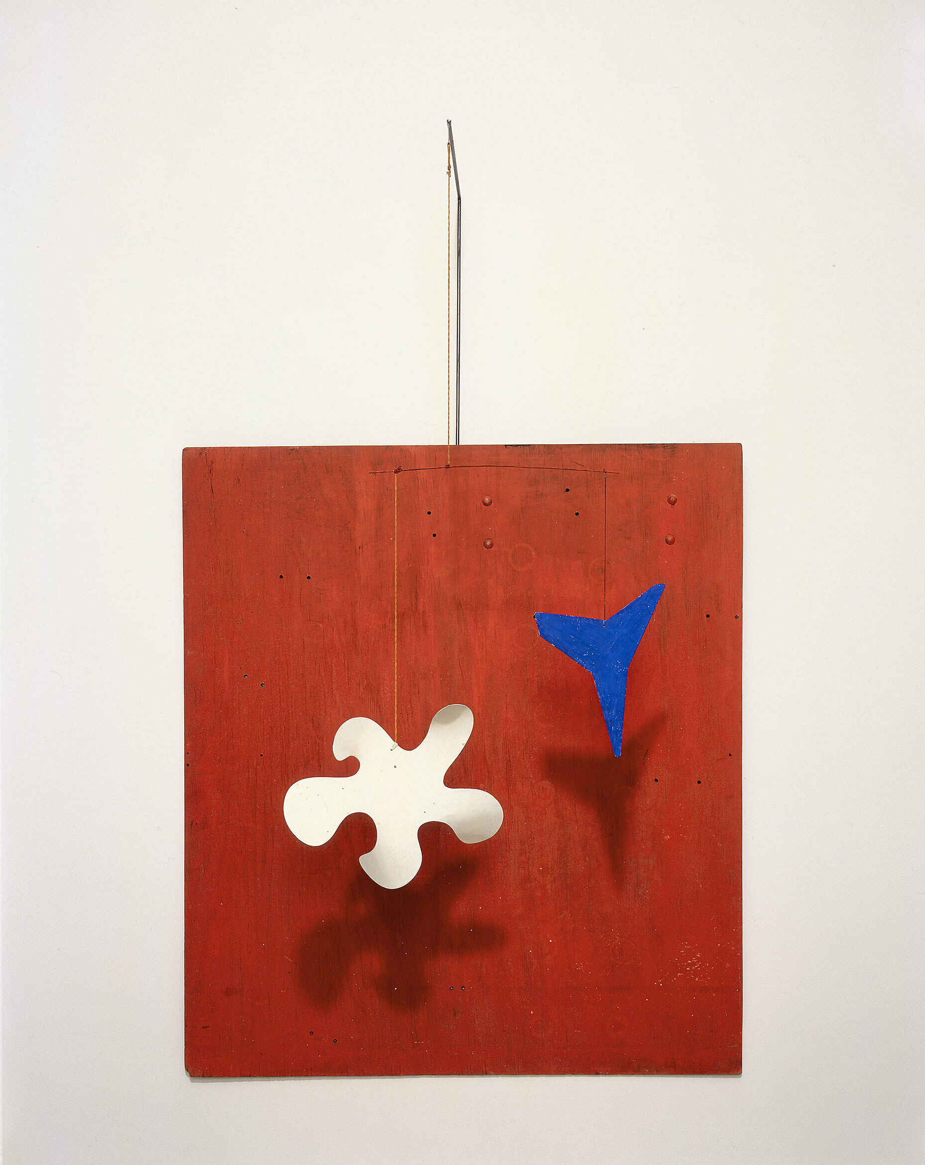 A work by Alexander Calder. A red square with abstract shapes in blue and white.