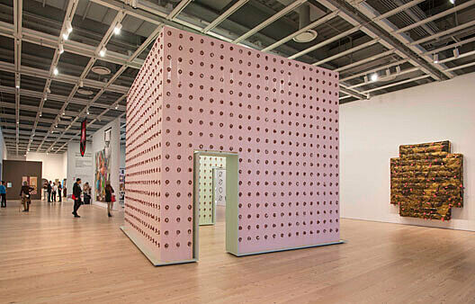 Structure made from four walls covered in grid pattern of bologna.
