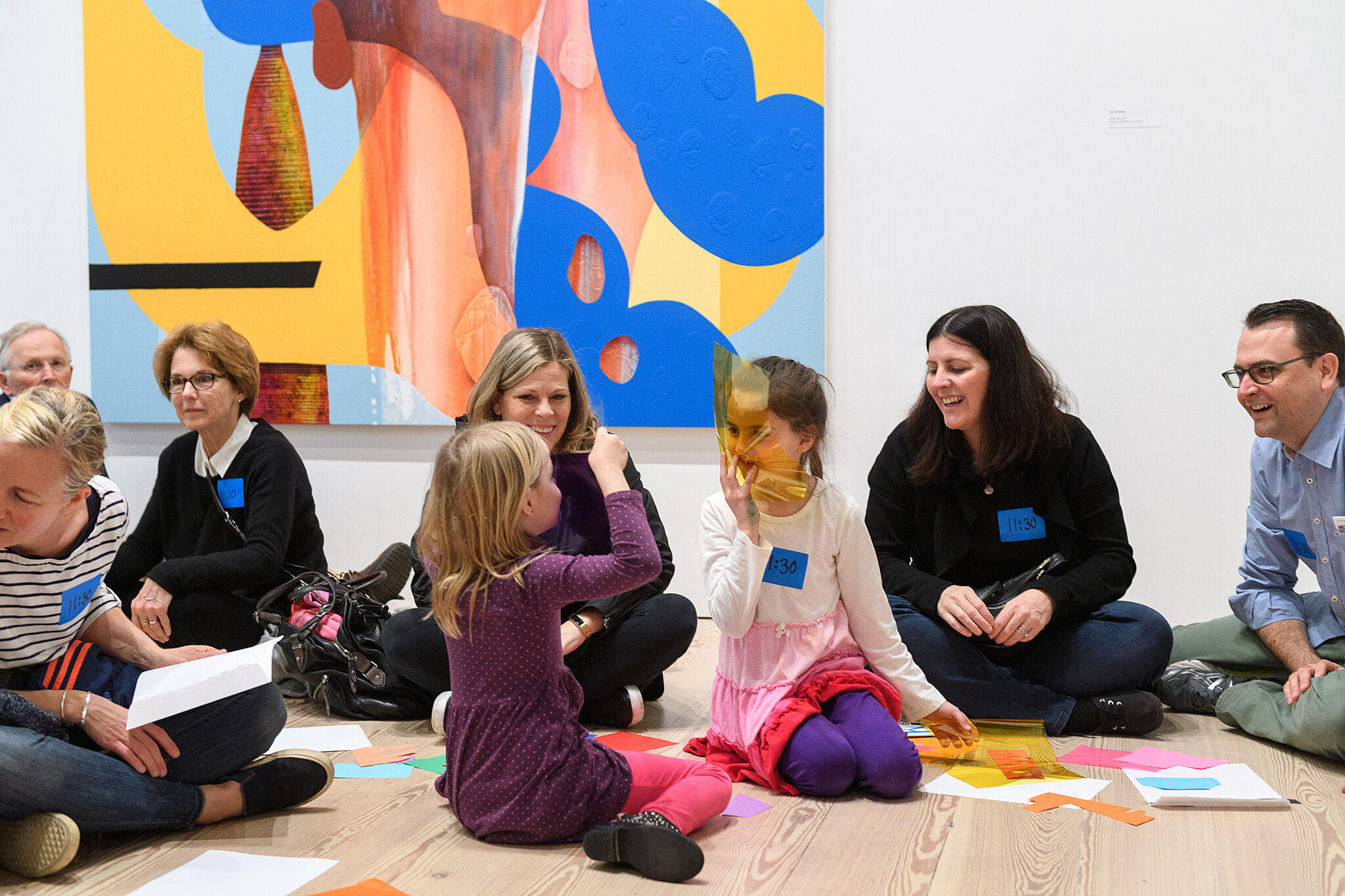 Children and adults sitting on the gallery floor with art materials.