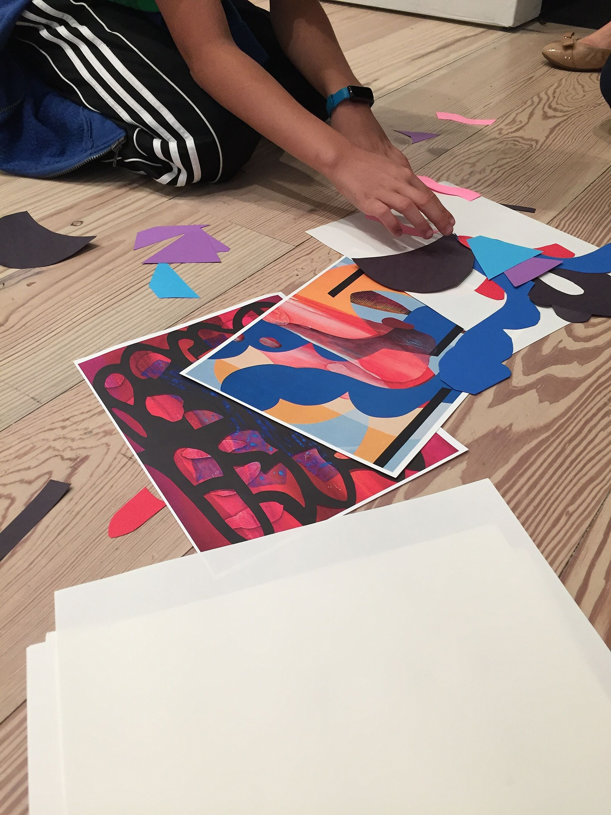A person sits on the floor making a collage.