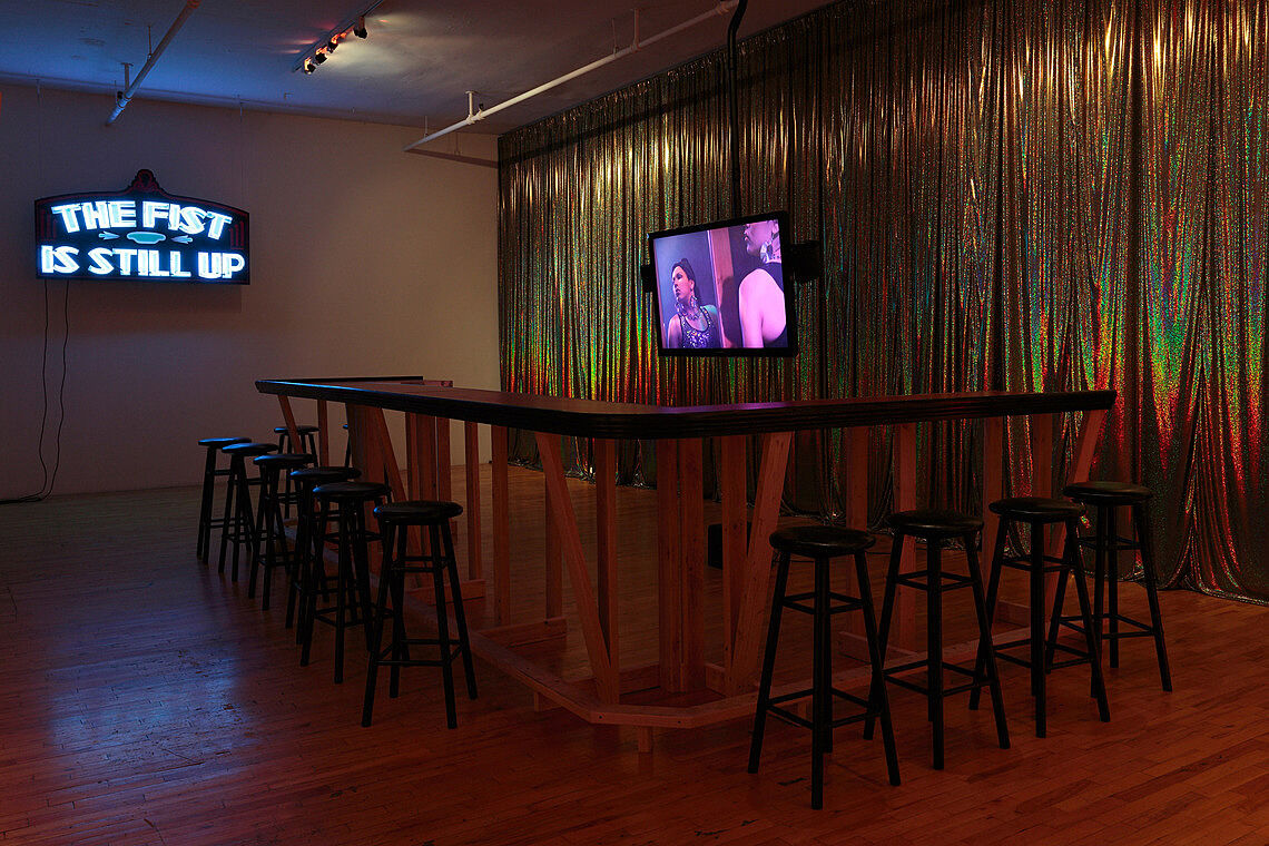 A room with a television, surrounded by an empty bar.