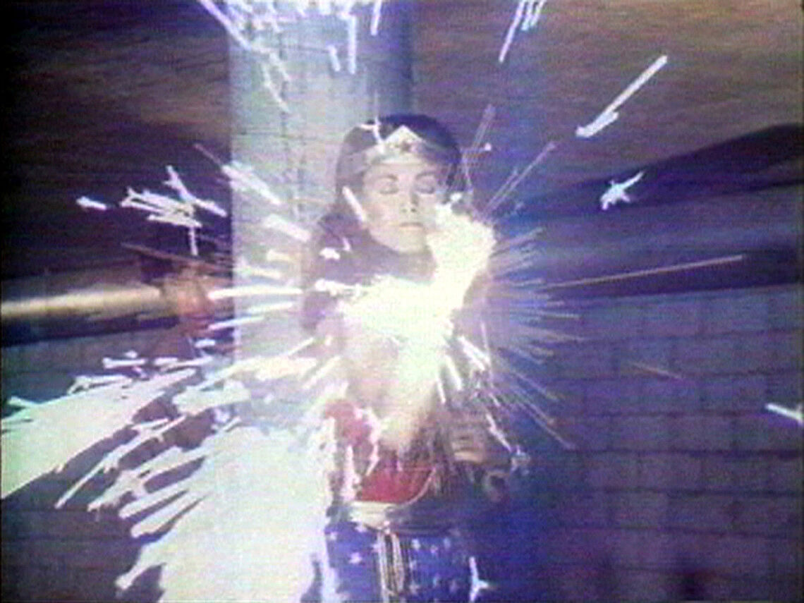 A still from a video featuring Linda Carter as Wonder Woman with her arm raised and sparks flying out of it